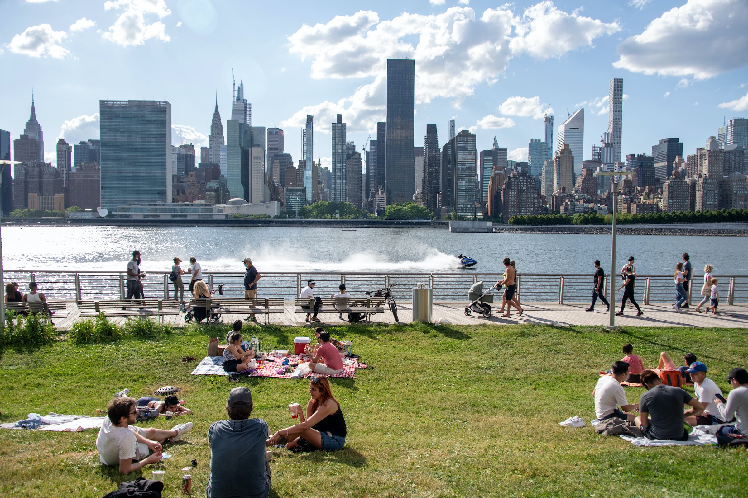 A riverside park facing the New York City skyline, full of people walking along the water or sitting in small groups on blankets on the grass.