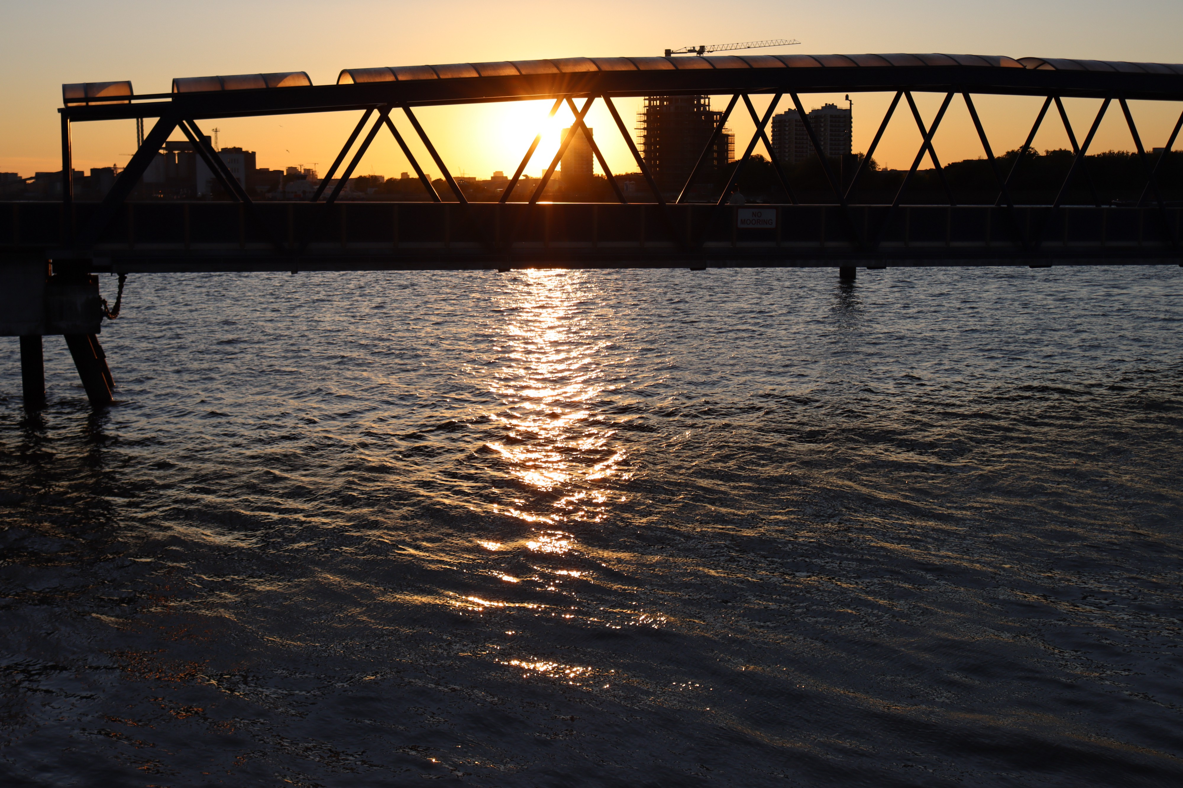 Sunset over the water with a bridge in silohuette