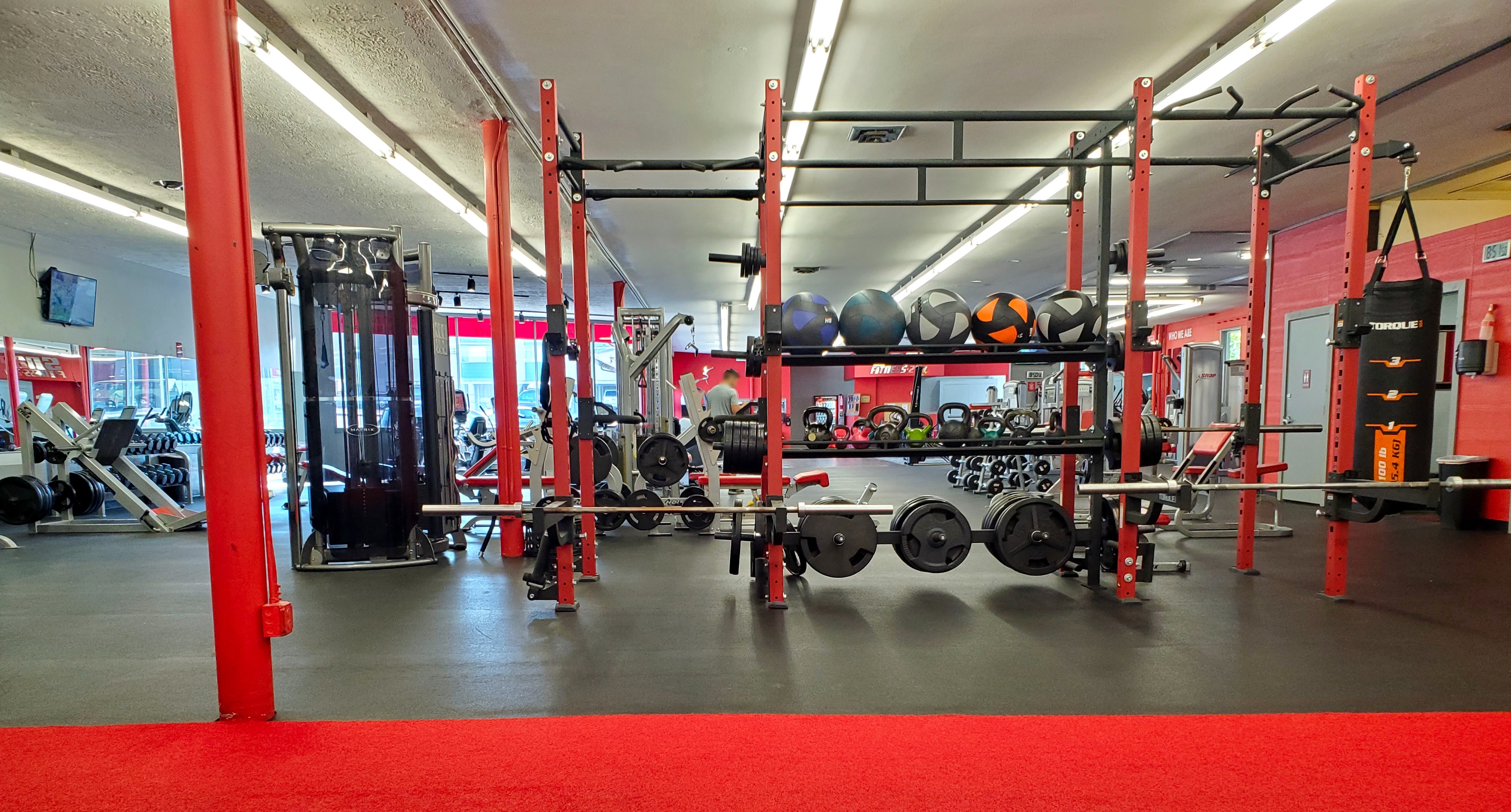 Brightly lit gym with weight equipment and machines.