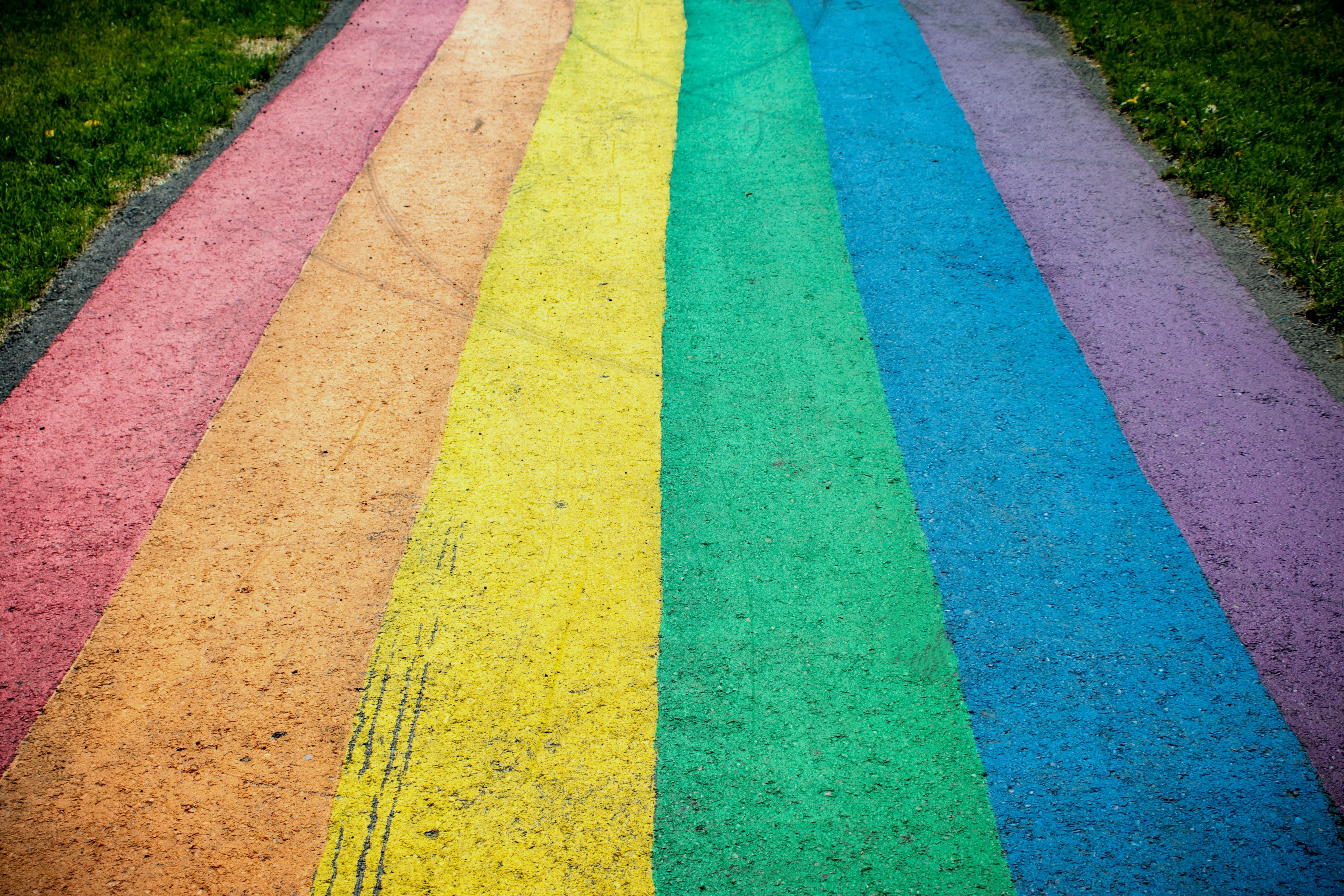 A sidewalk filled with rainbow stripes in chalk.