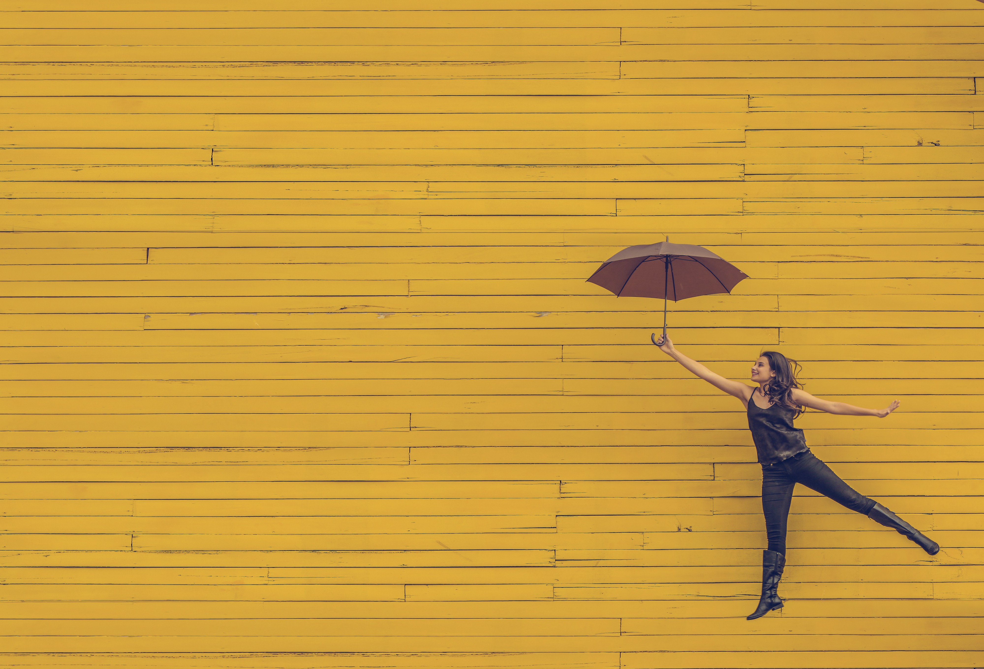 Woman suspended with umbrella against yellow wall. Trust, self-management, holacracy, sociocracy, teal organizations