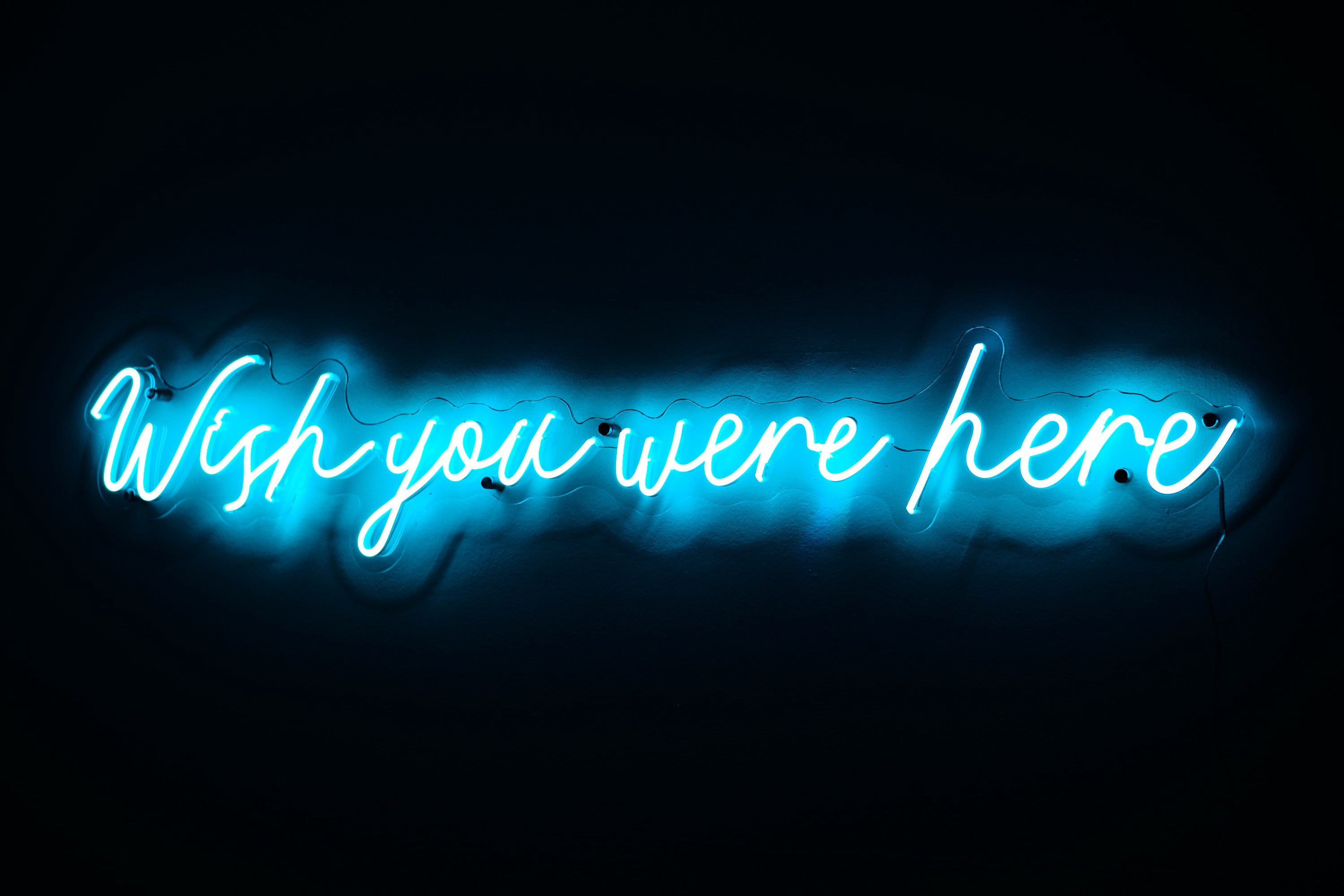 """Blue neon sign saying """"Wish you were here"""""""