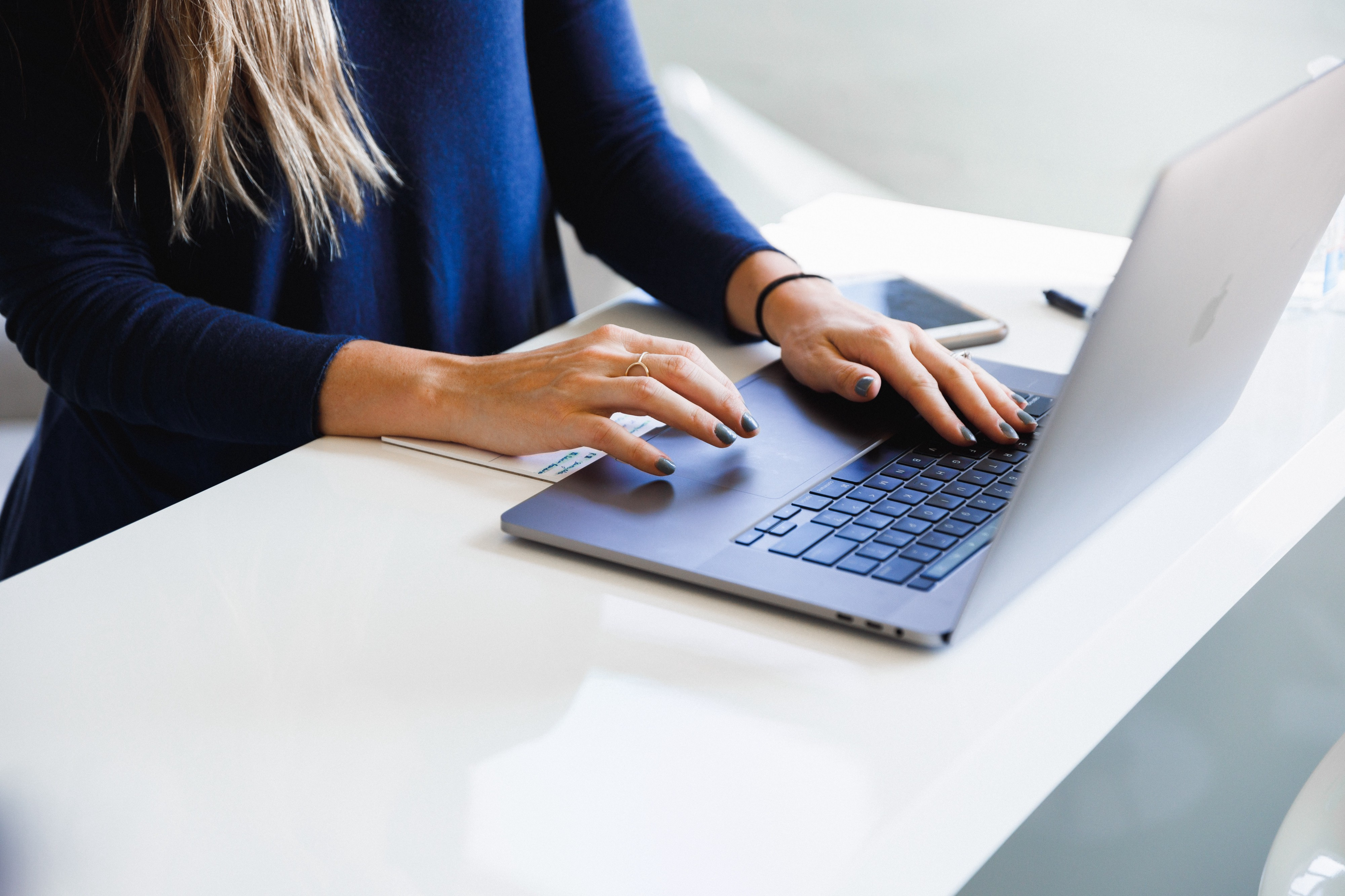 A person typing something into the laptop while standing by the white table.