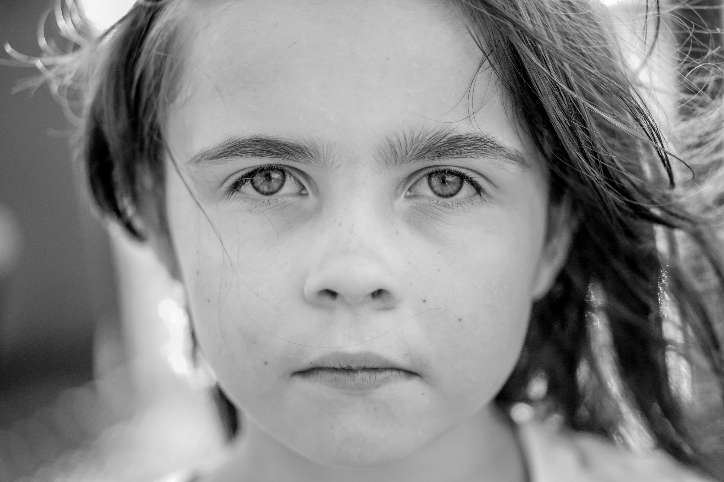 little girl looking at the camera, black and white photo