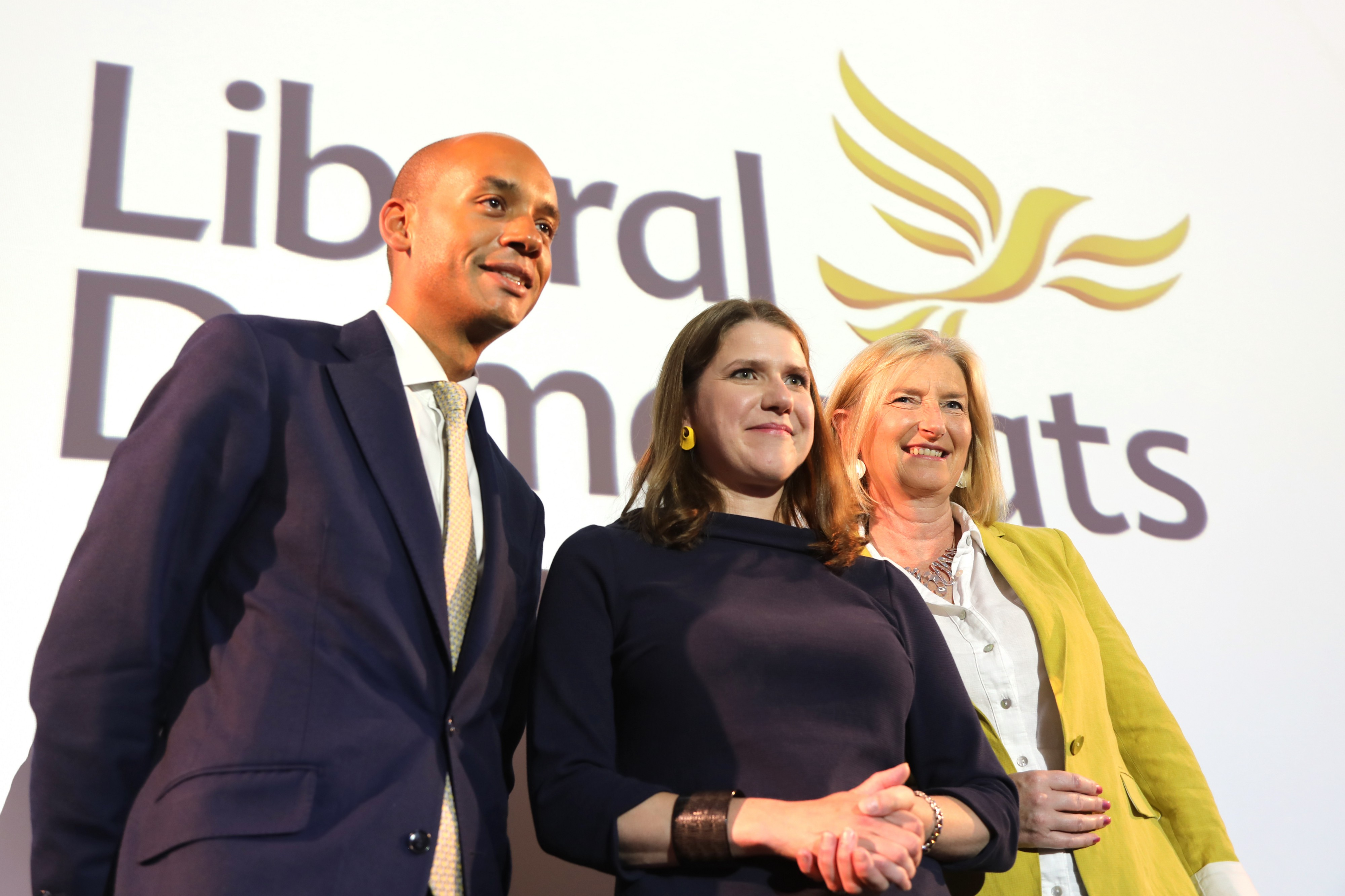 From left to right, Chuka Umunna, Jo Swinson and Sarah Wollaston posing in front of a a sign saying 'Liberal Democrats'