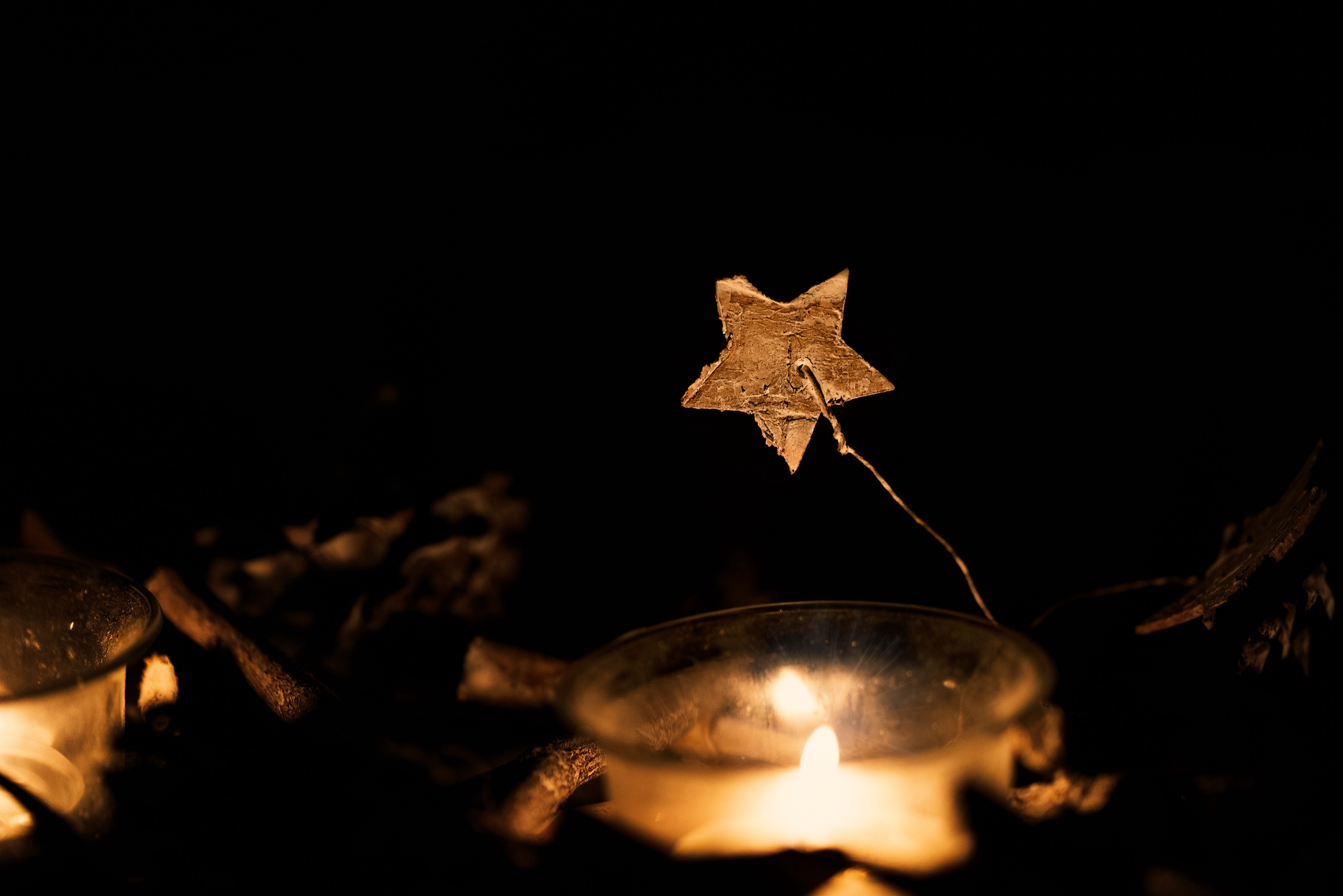 Small gold star suspended above candle flame with black background