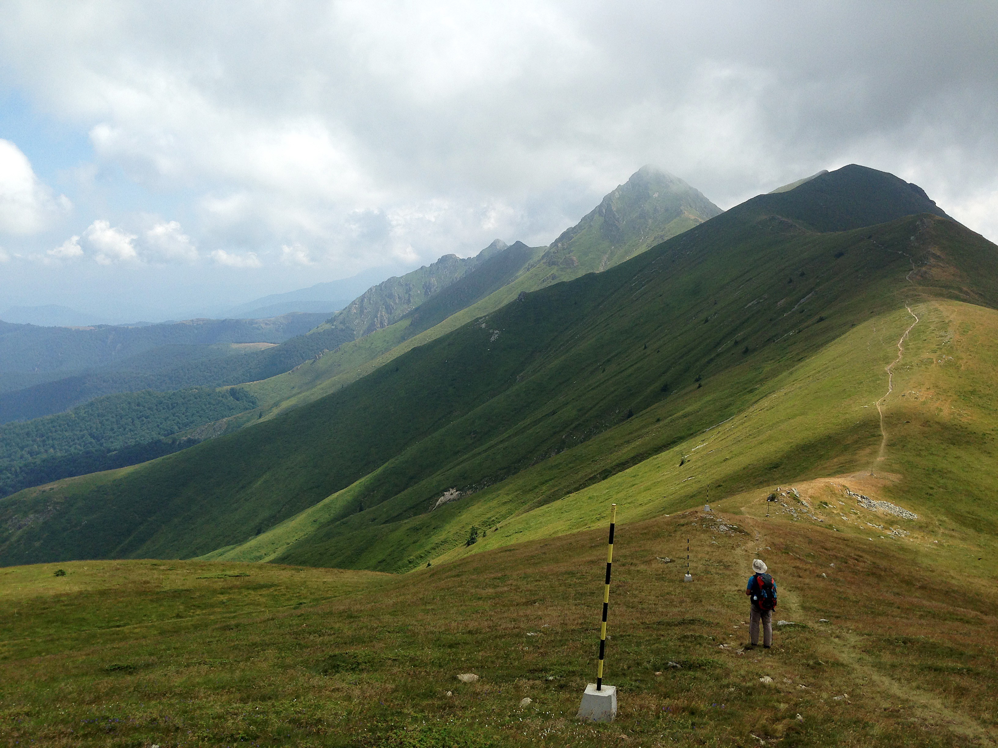 A green mountain range, in the foreground is a hiker. In the distance a path goes on the ridge, peaks are in clouds.