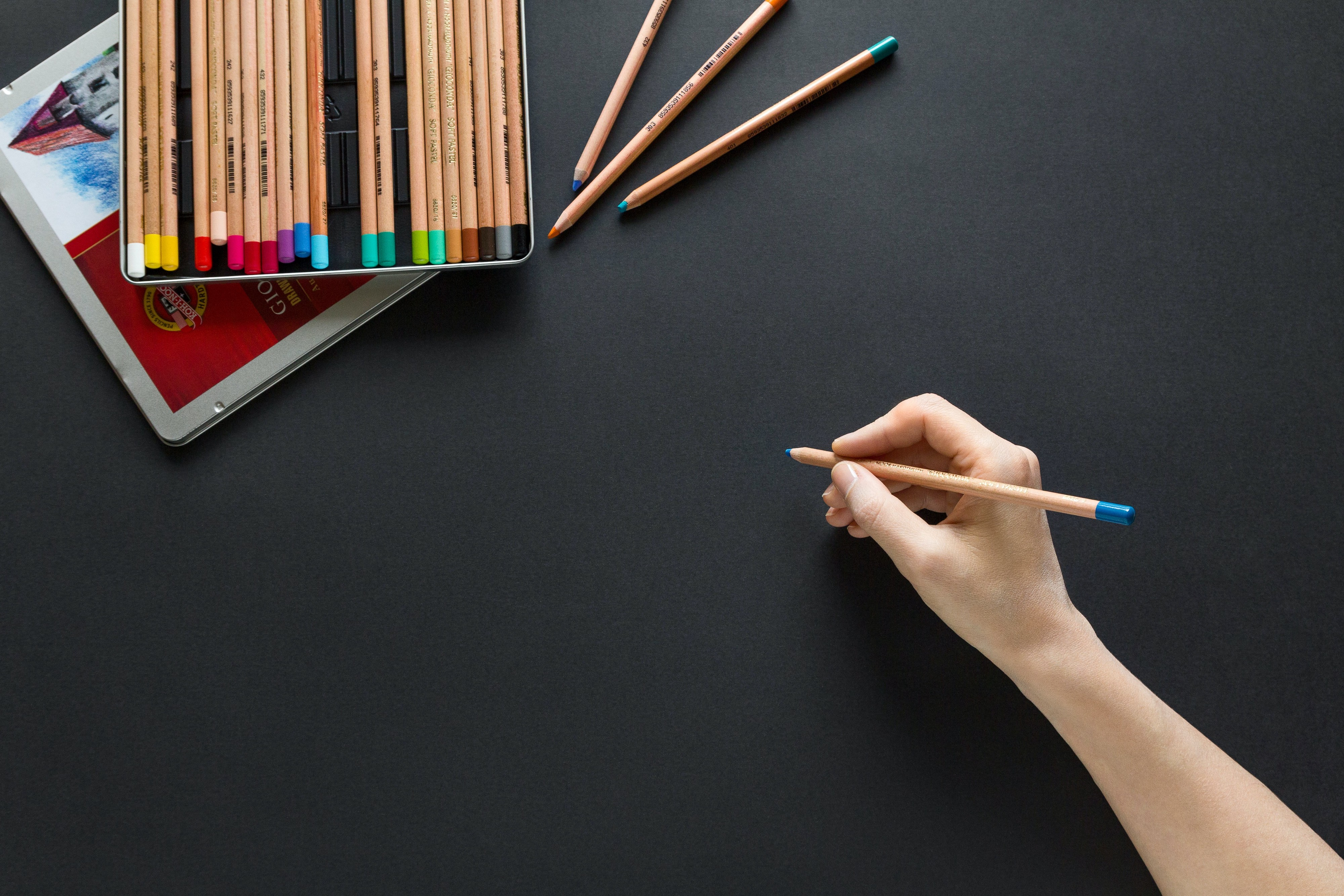 An image of a box of colored pencils on a black background. A hand holds one of the pencils near the middle.