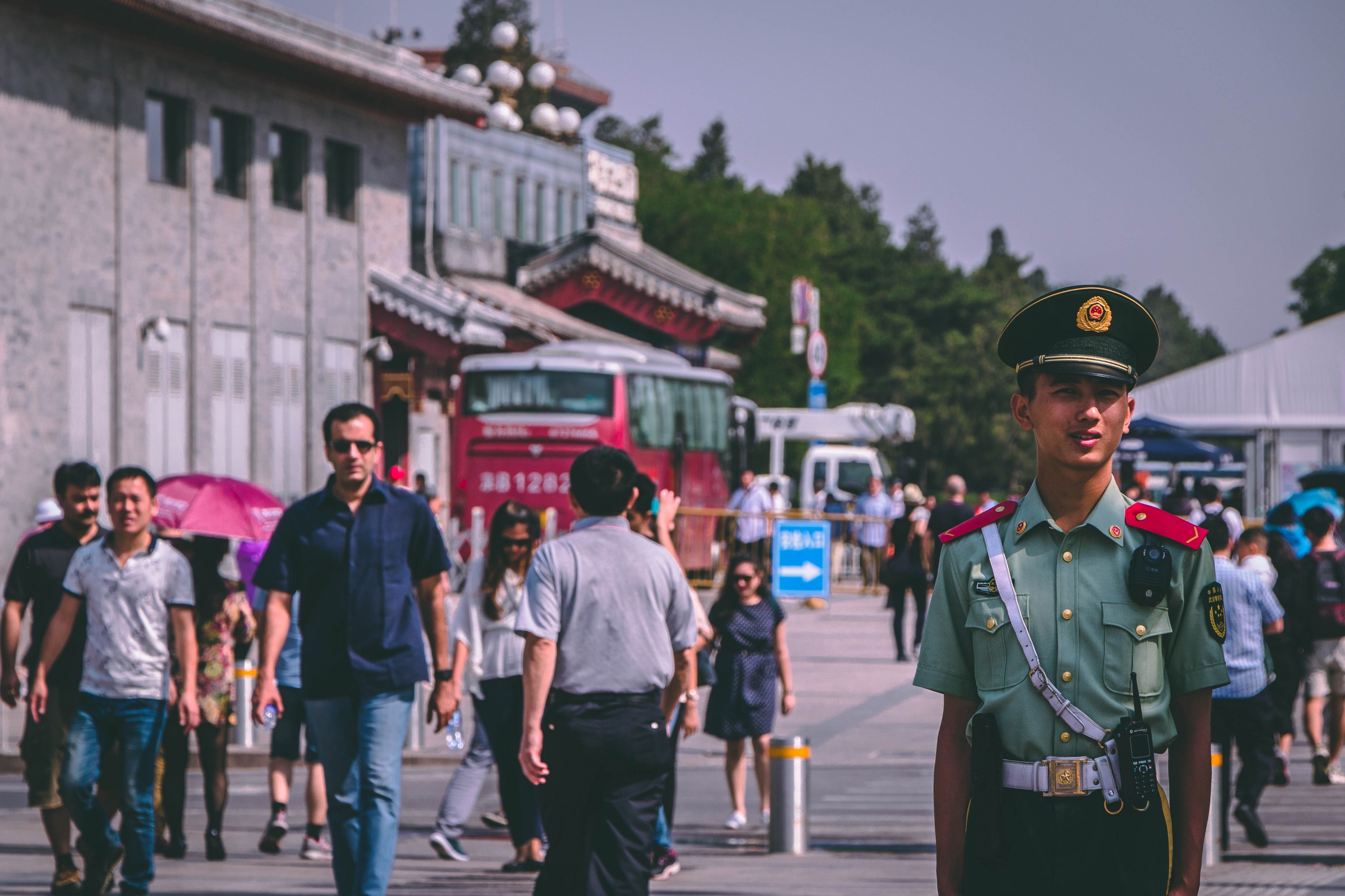 A chinese police officer standing in front of people walking past in front of a grey building with a red coach alongside