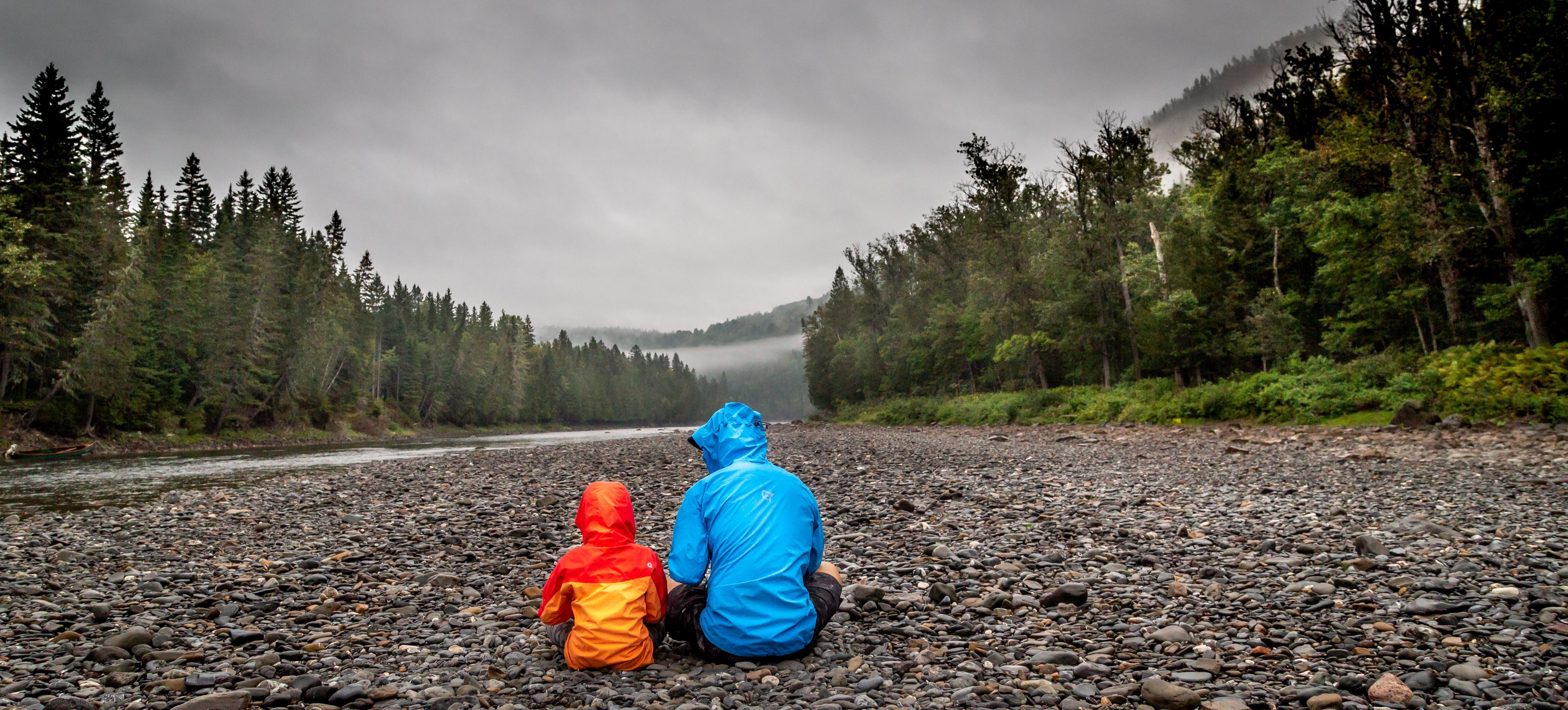 A father and child sitting on an expanse of pebbles, back to the camera. In the distance is a river and trees on both banks.