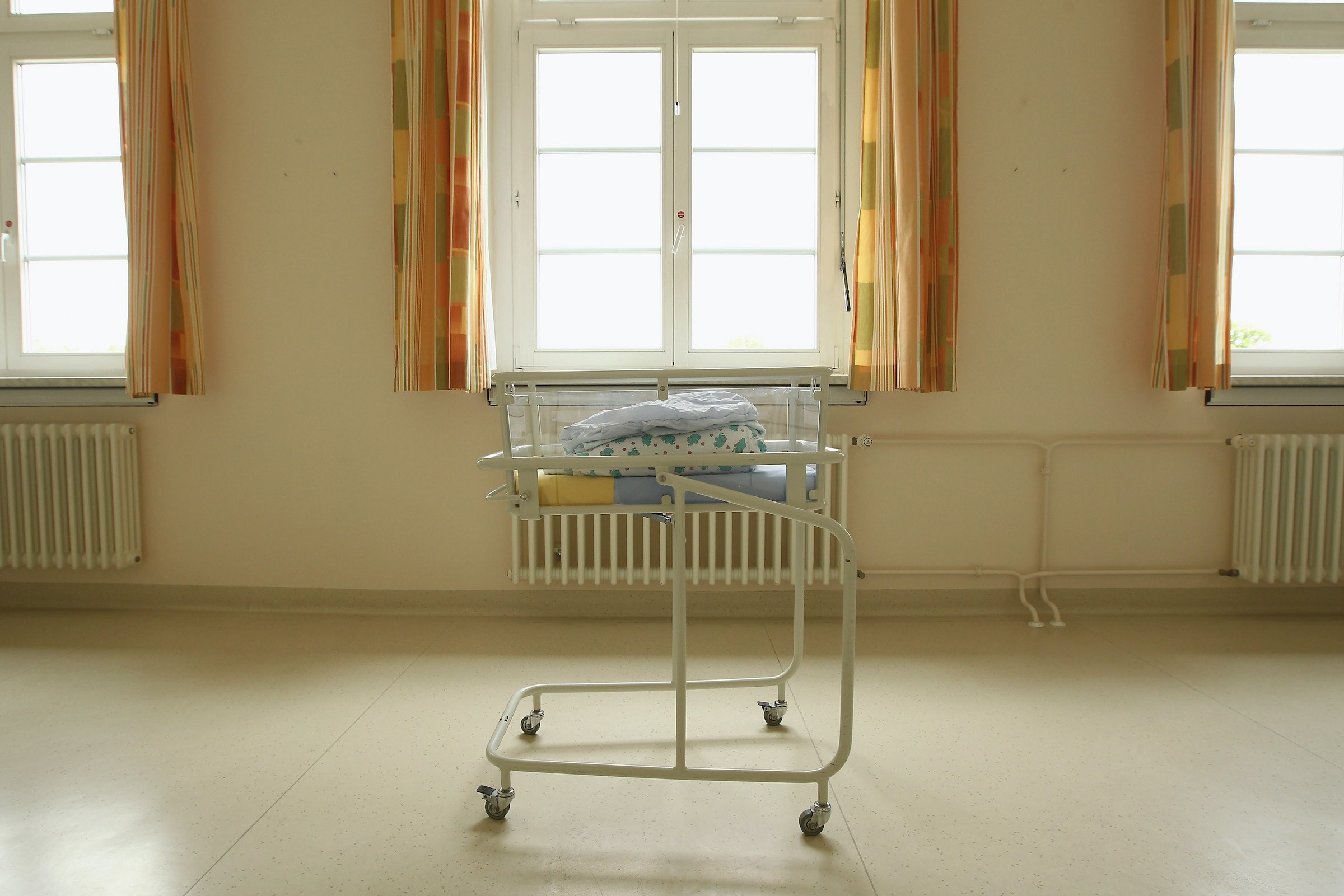 An empty baby bed in front of a window in a maternity ward.