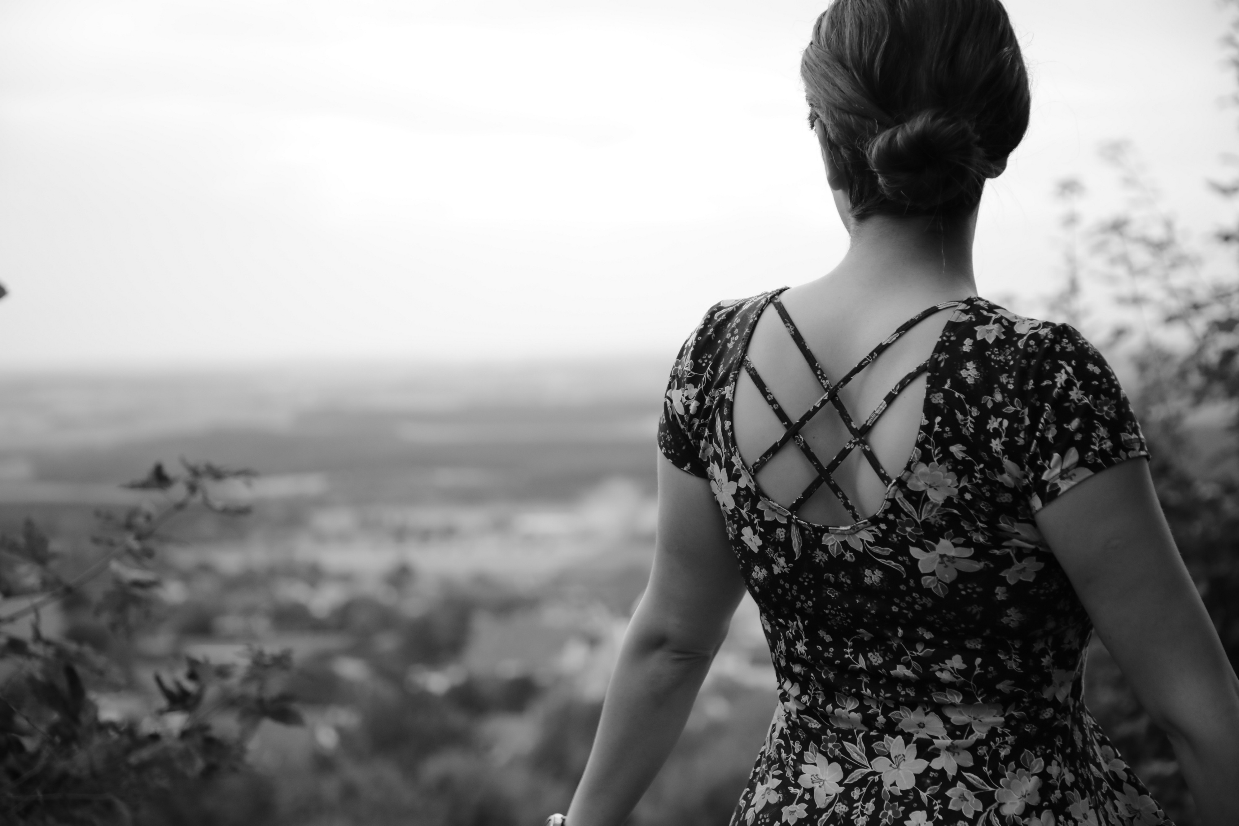 Back view of a woman wearing a dress and looking at the countryside