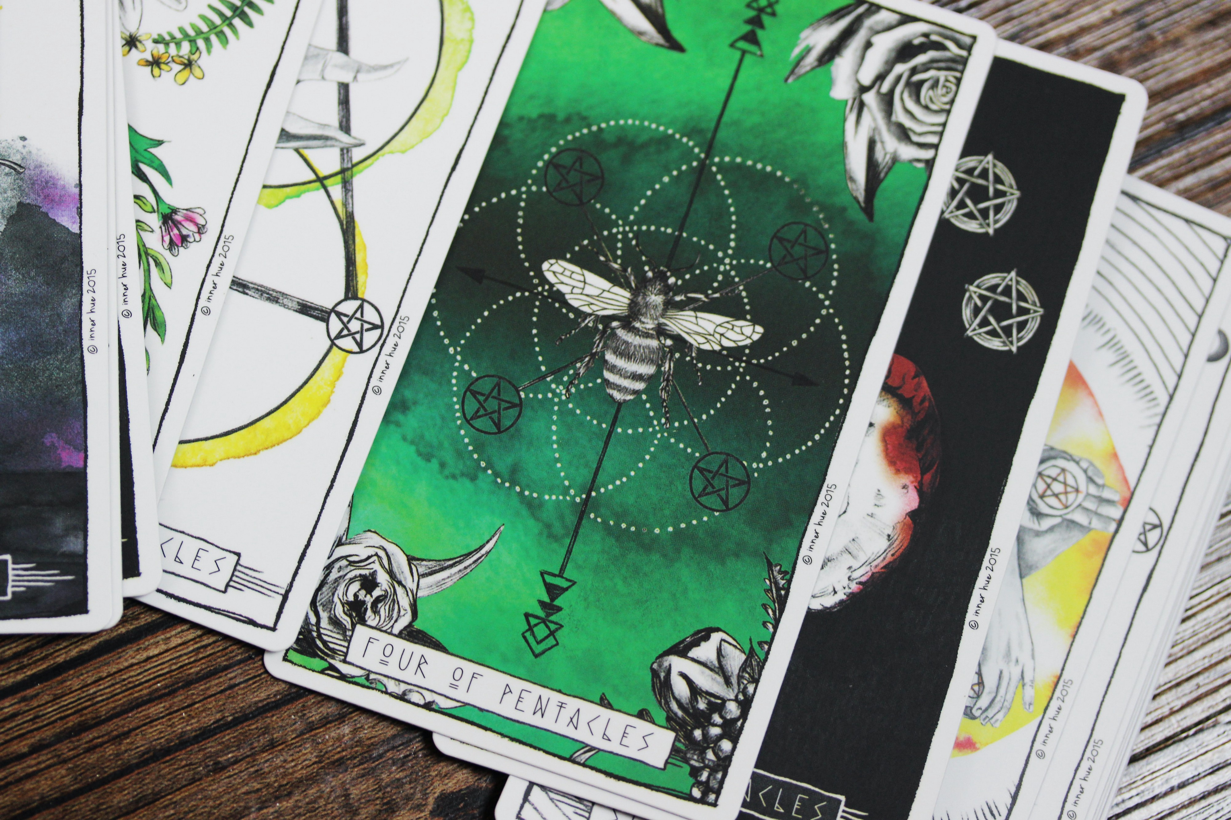 Tarot cards spread on a wooden surface; the main card that's visible is the Four of Pentacles, green with a bee on it.