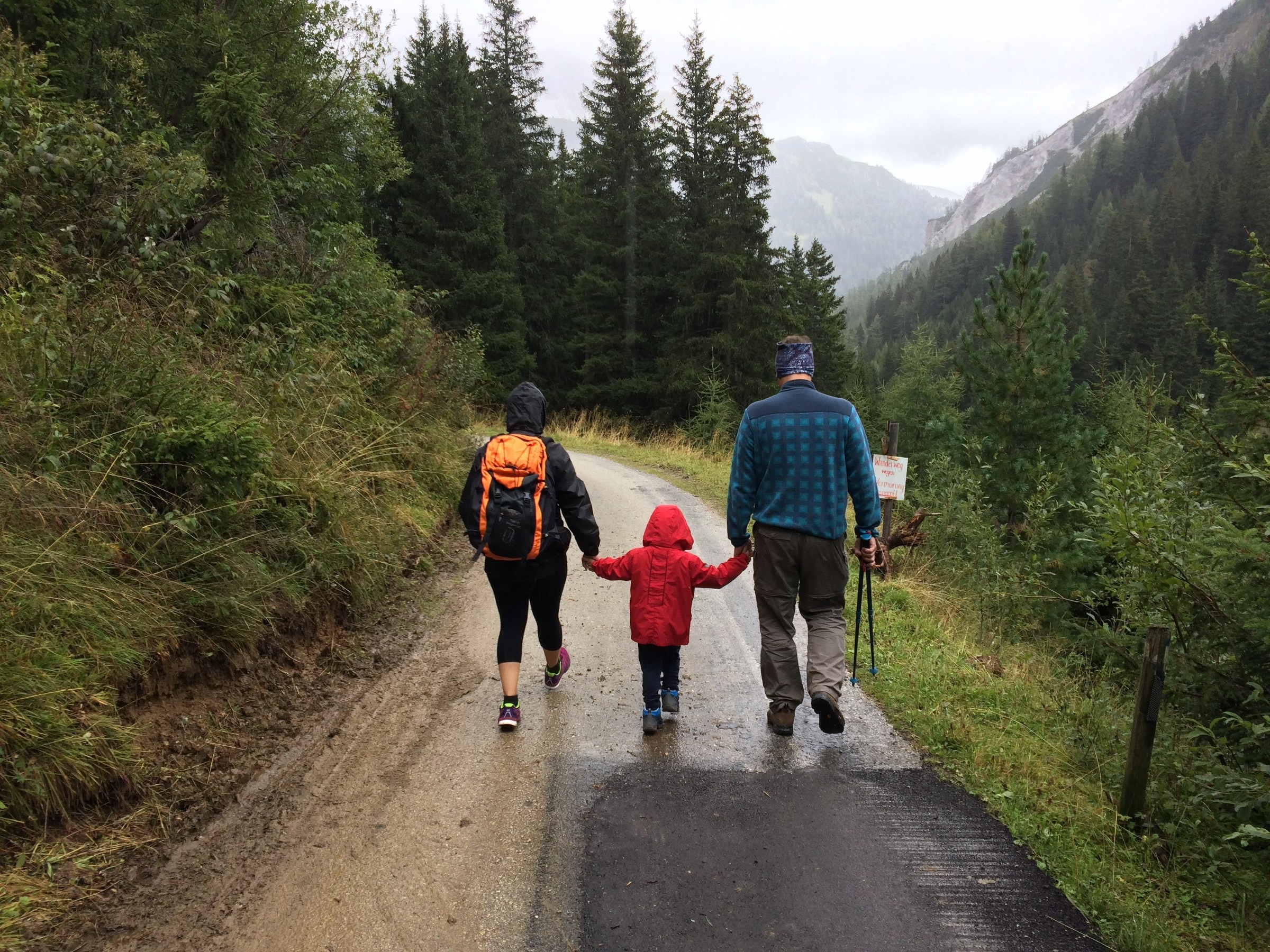 Family walks together down a mountain road, with two parents holding a child's hands in the middle.