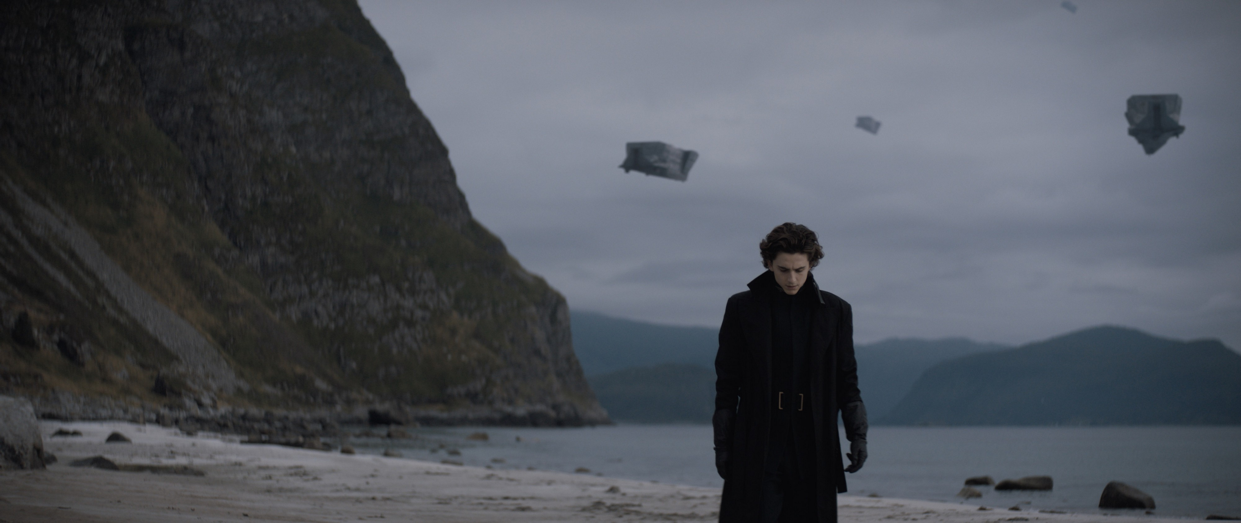 Paul Atreides (Timothée Chalamet) walking in the desert with two aircraft in the cloudy sky behind him.