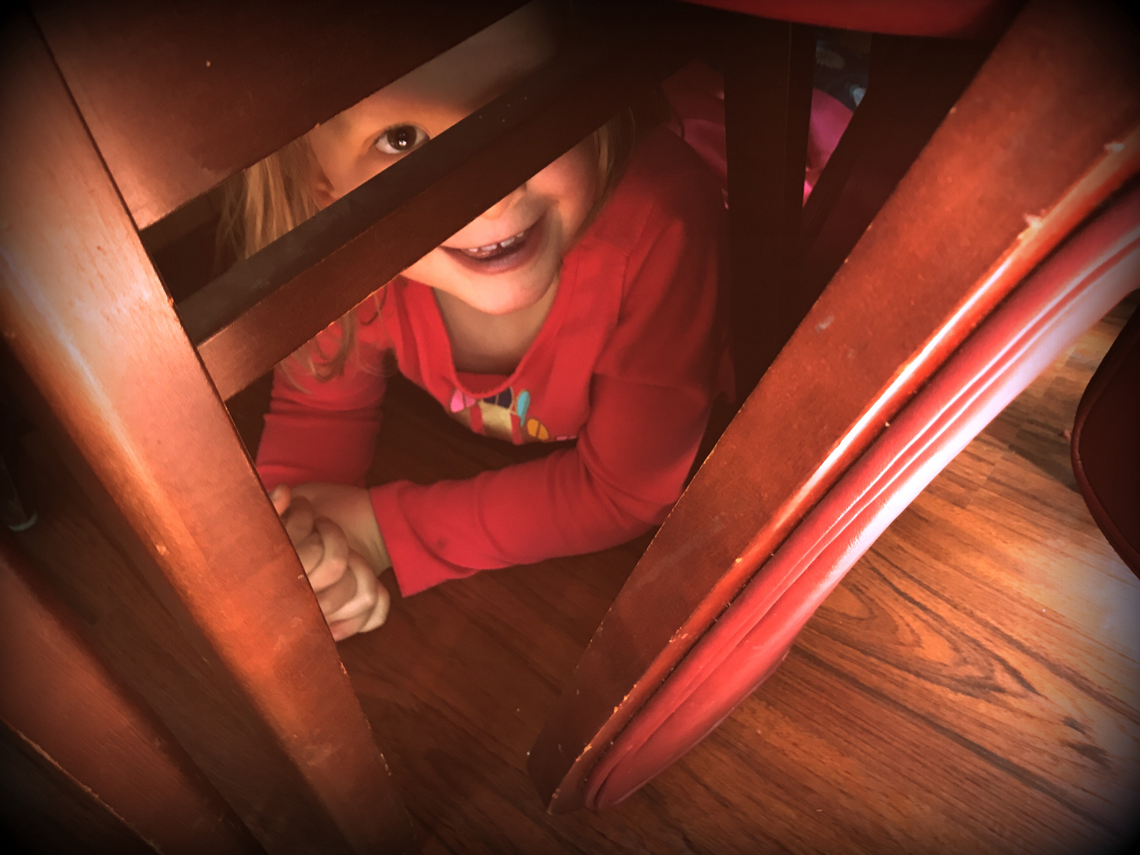 Photograph of a little girl hiding under some dining room chairs looking up with a smile on her face after being discovered