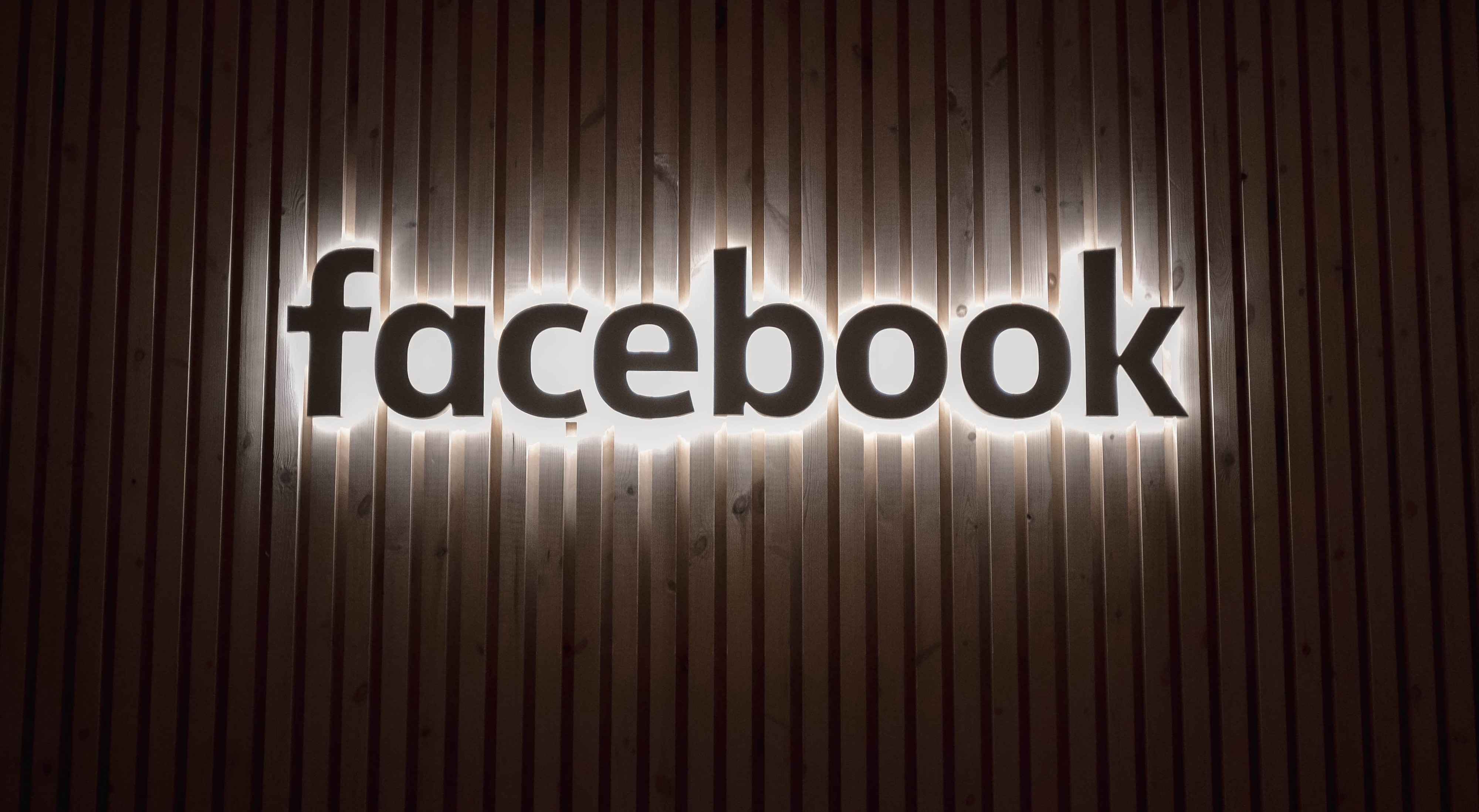 Photo with the word Facebook as a sign wrote in the colour black with white lighting behind it