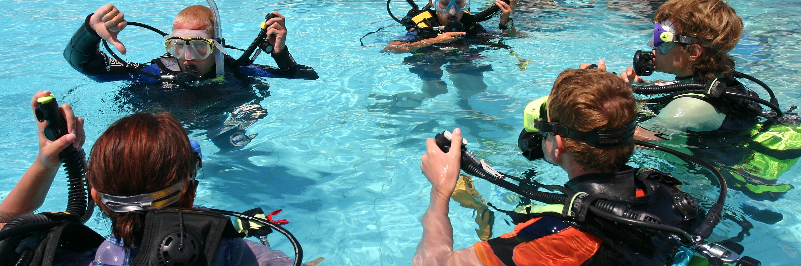 A scuba diving instructor leading a class in pool exercises.