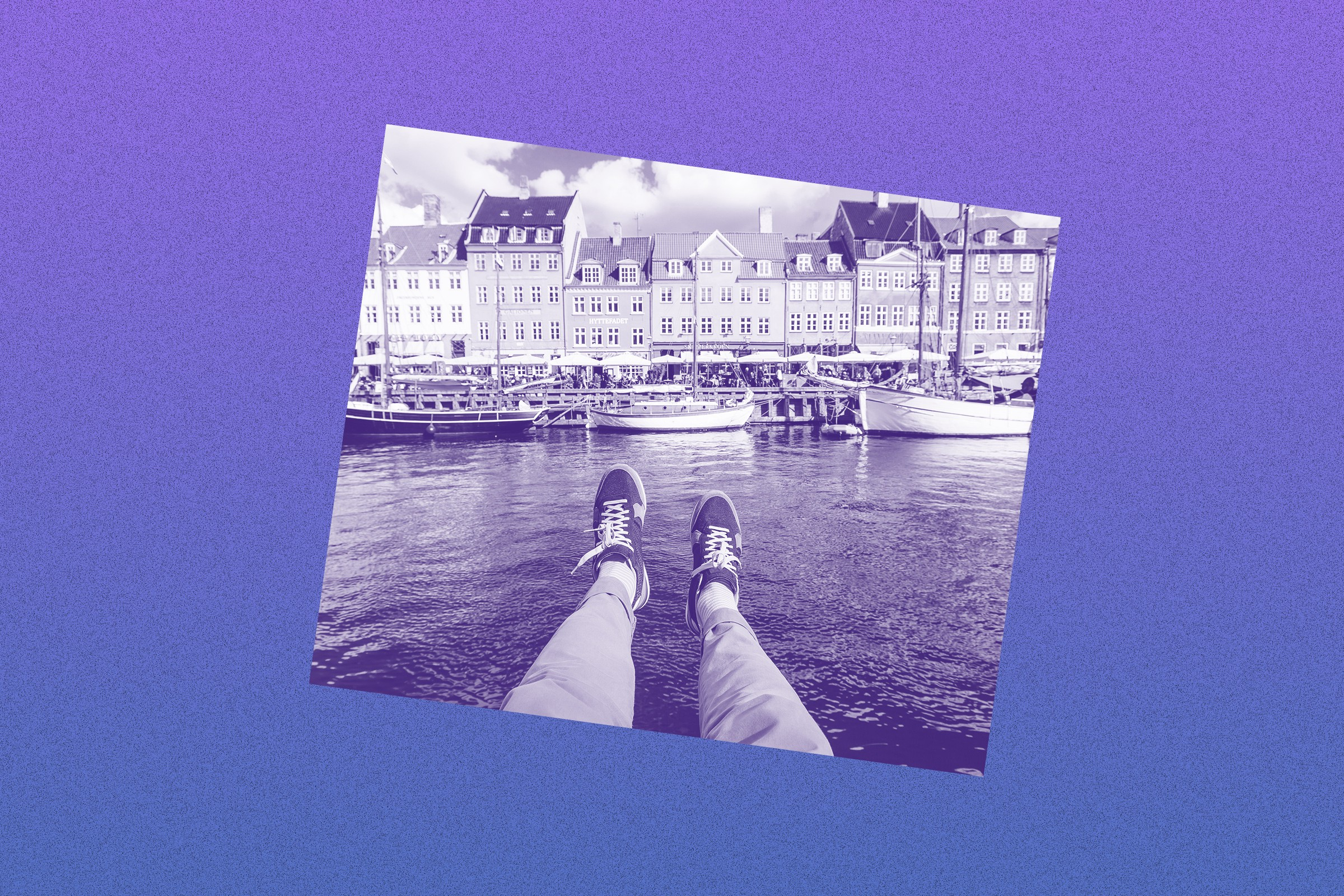 Filtered image of a person's legs dangling over water with European buildings in the background.