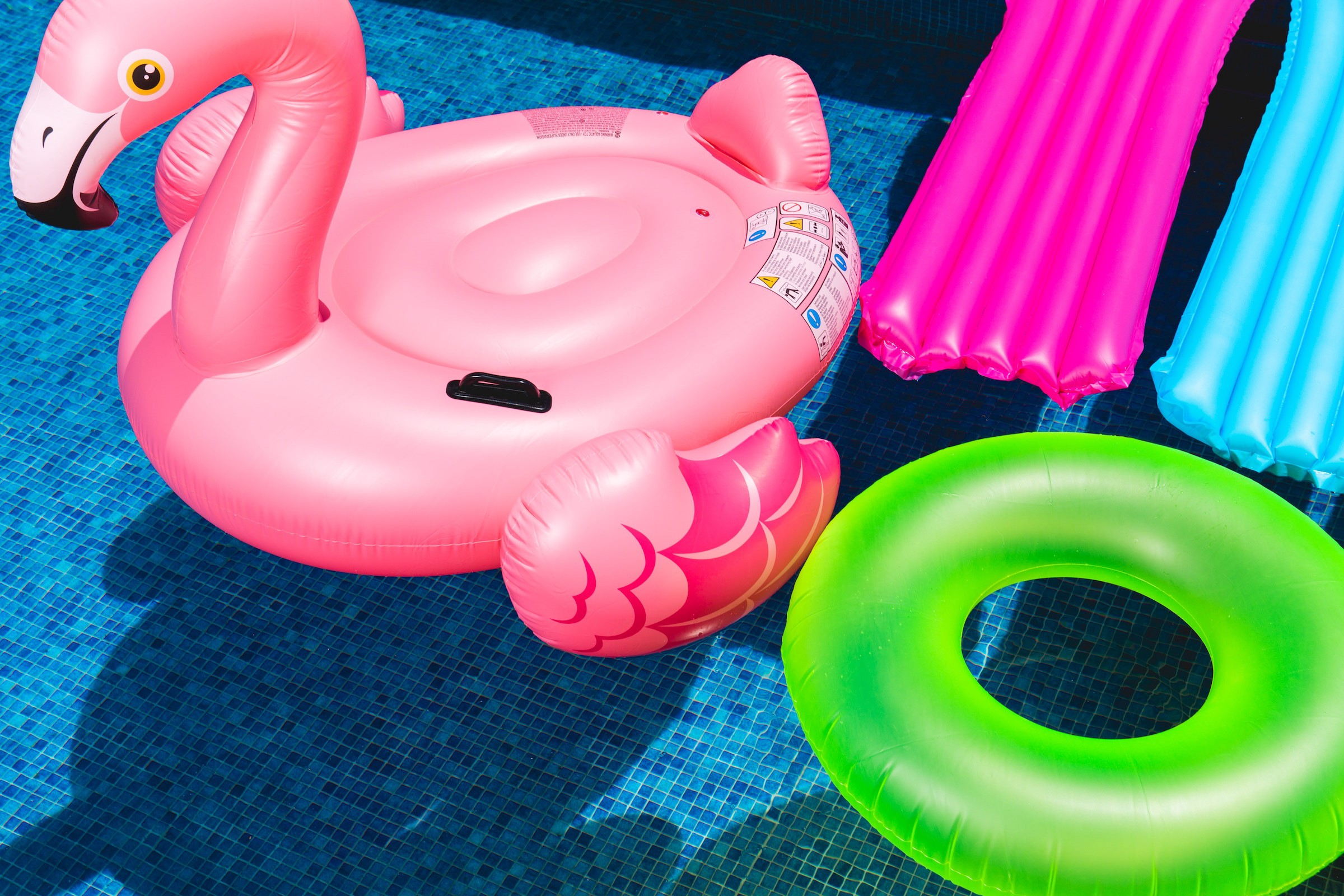 An inflatable flamingo, inner tube, and two pool floats in a pool