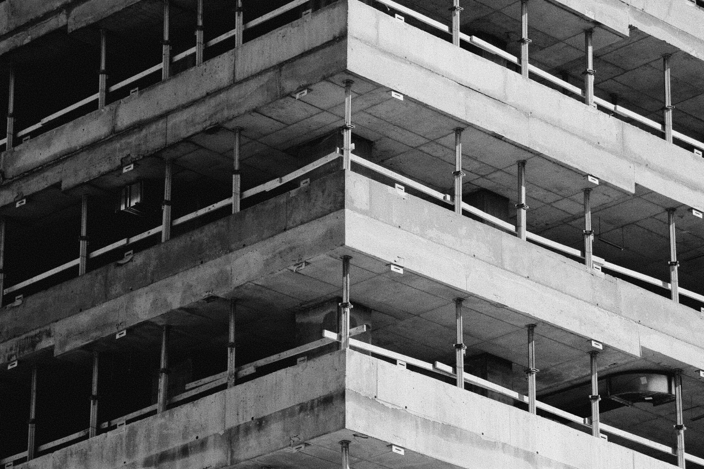 A building under construciton. With very visible basic elements of concrete and support structures.