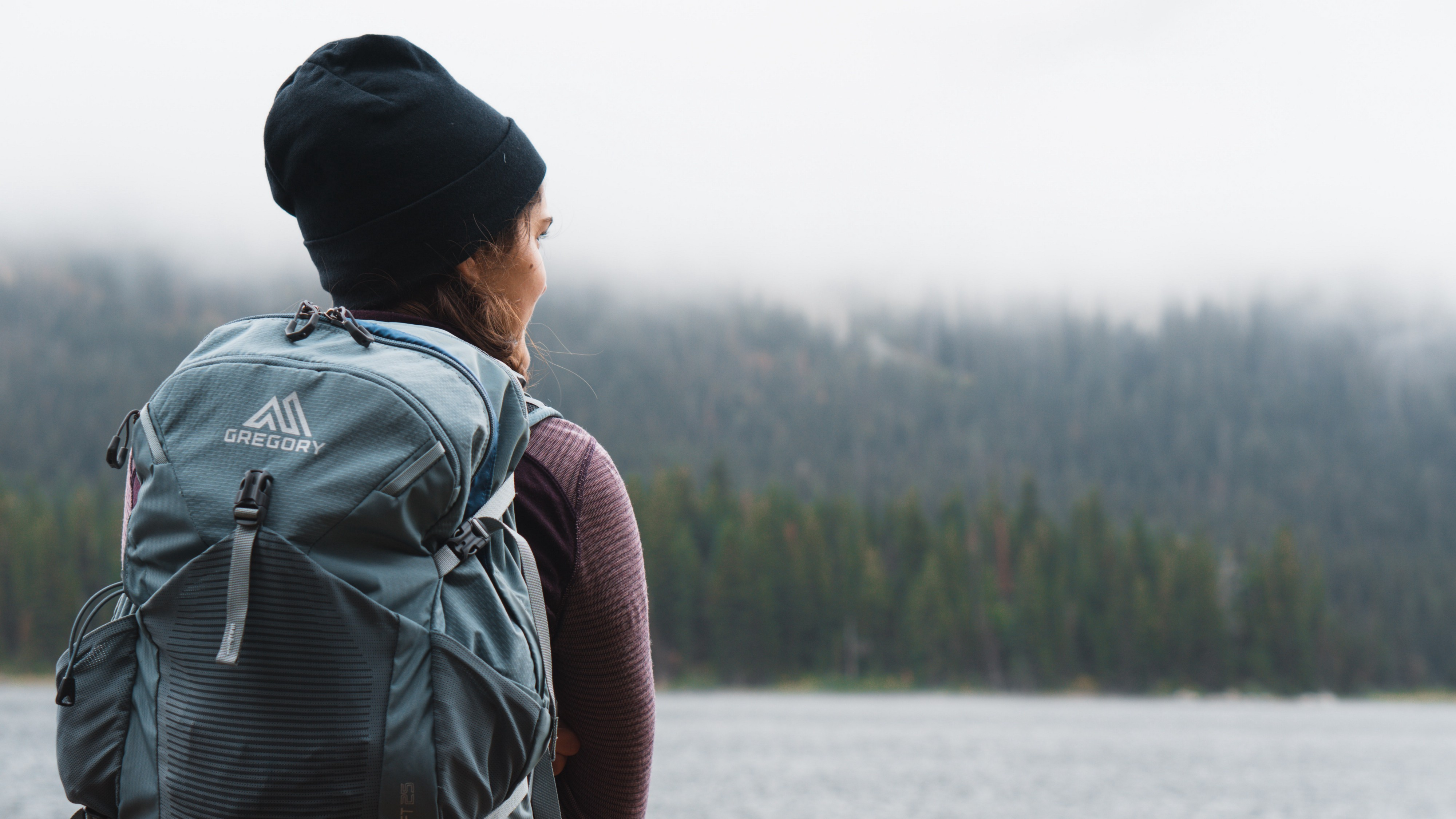 Woman with backpack and snow hat looking forward to a river and mountain she has to cross