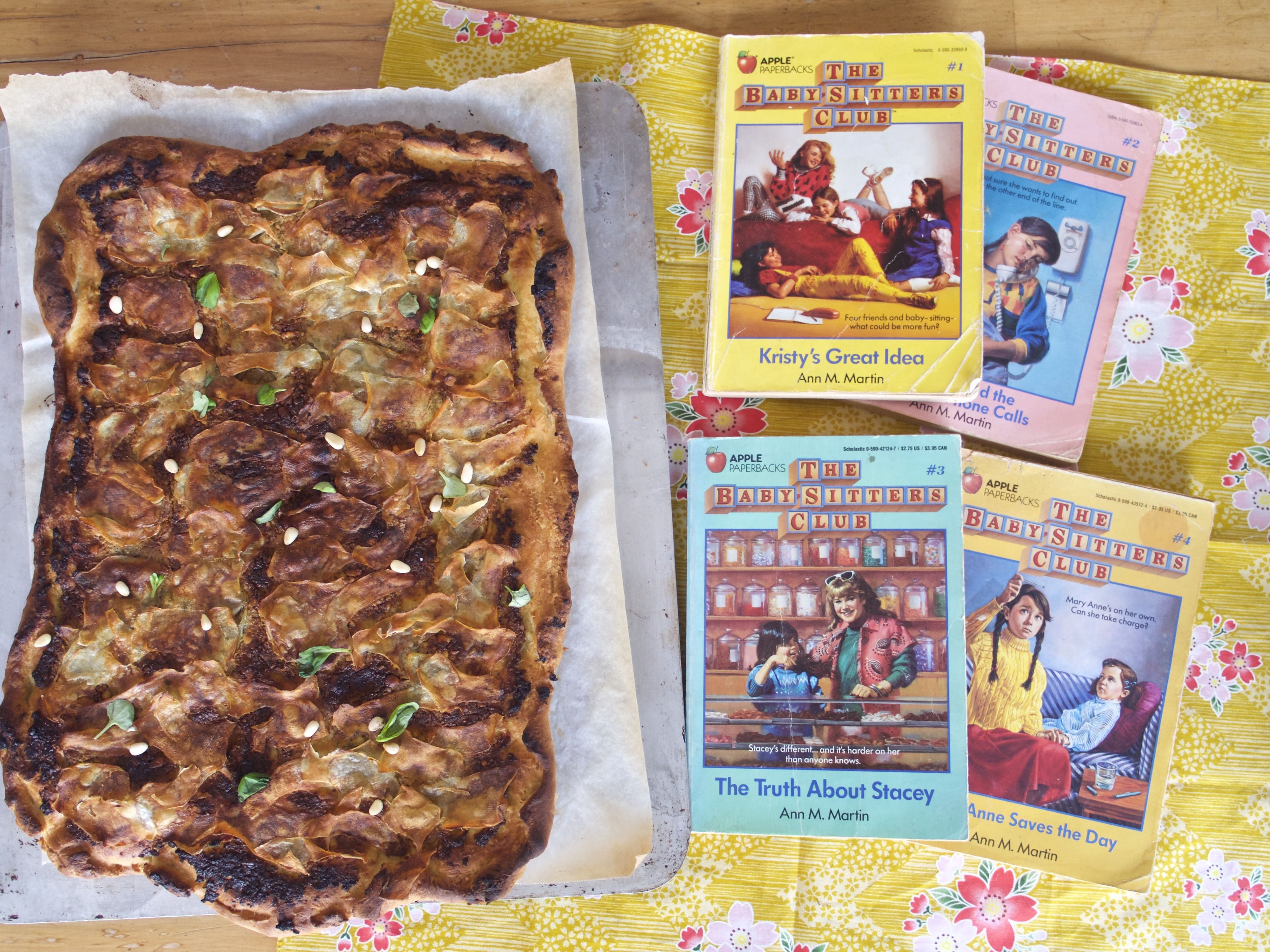 A rectangular sheet pan pizza with crispy, browned potatoes and basil and pine nuts, next to 4 retro Baby-Sitters Club books