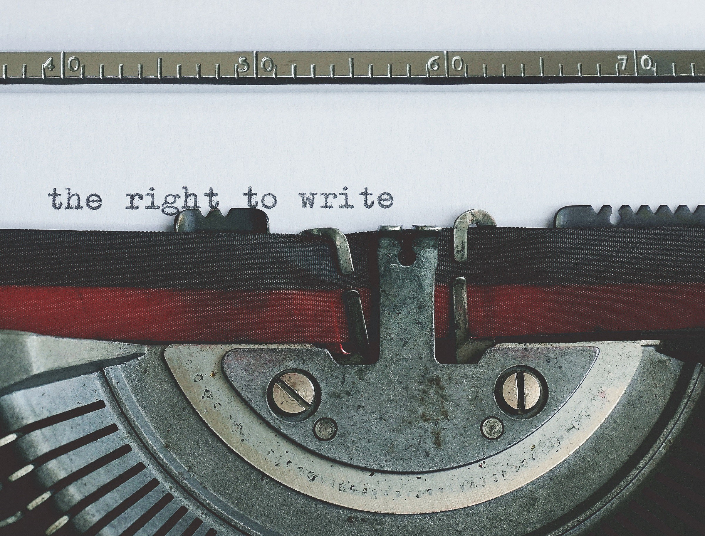 """Close shot of old typewriter holding a piece of paper that reads """"the right to write."""""""