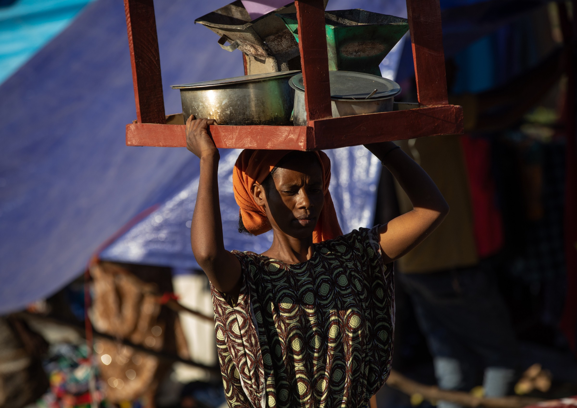 A woman balances a small, upside-down table on her head, using it to carry things; there's a blue tarp tent in the background