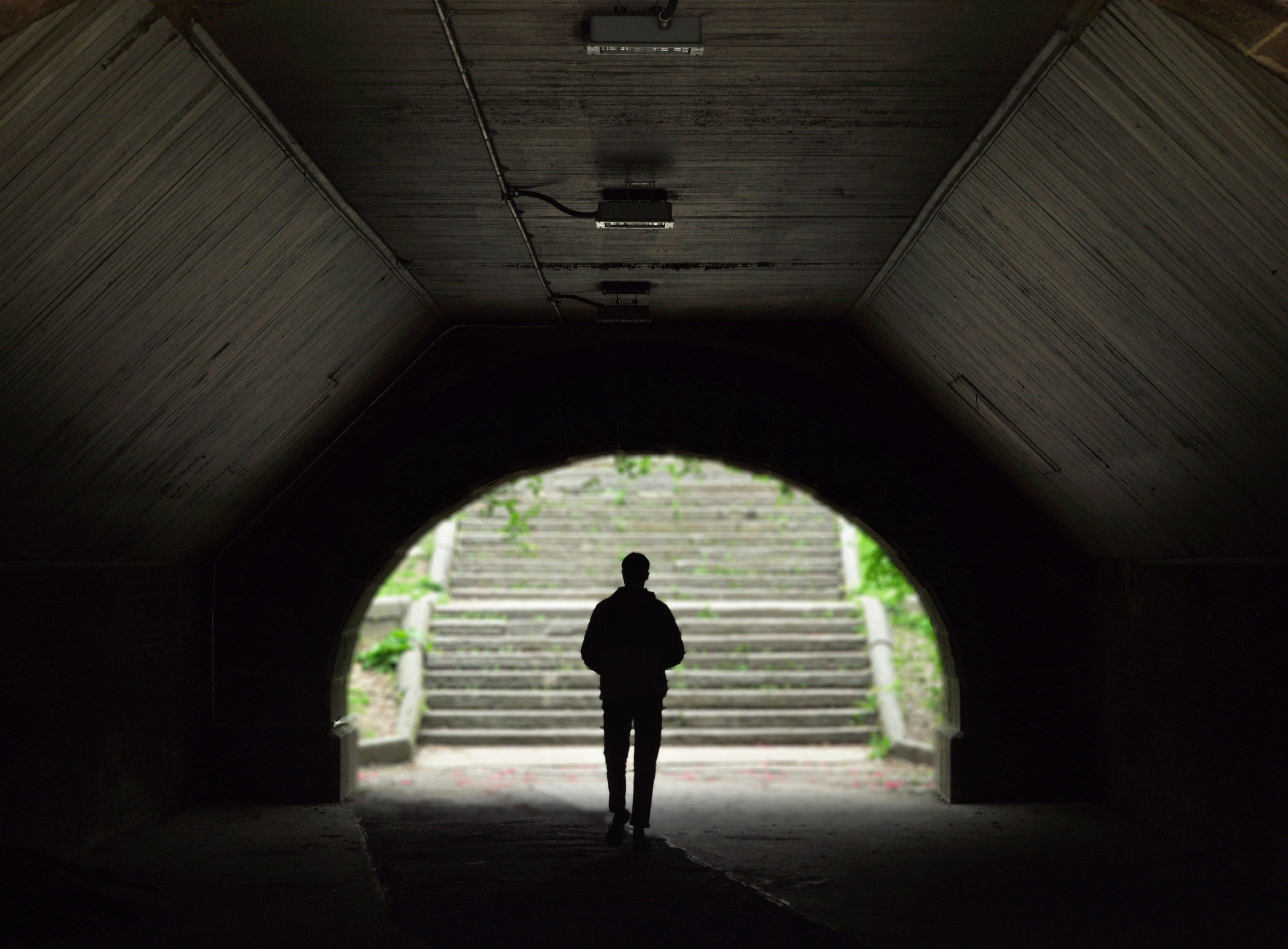 A silhouetted person walking to the end of a tunnel where stone steps lead upward.