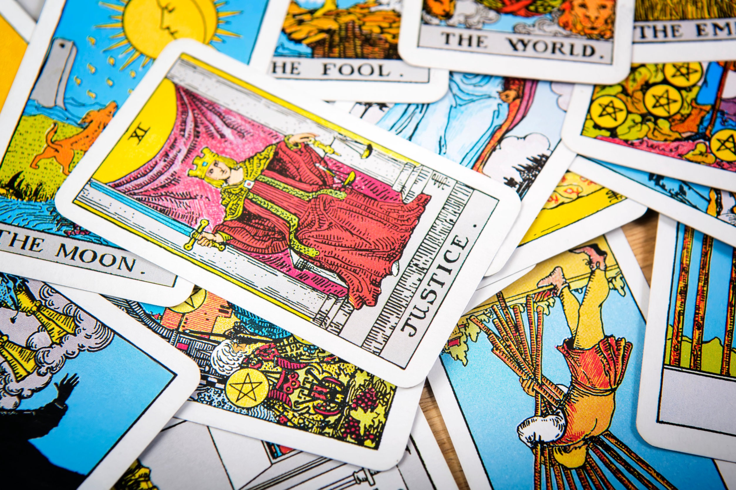 """Tarot cards scrambled facing up, the card marked """"Justice"""" on top"""