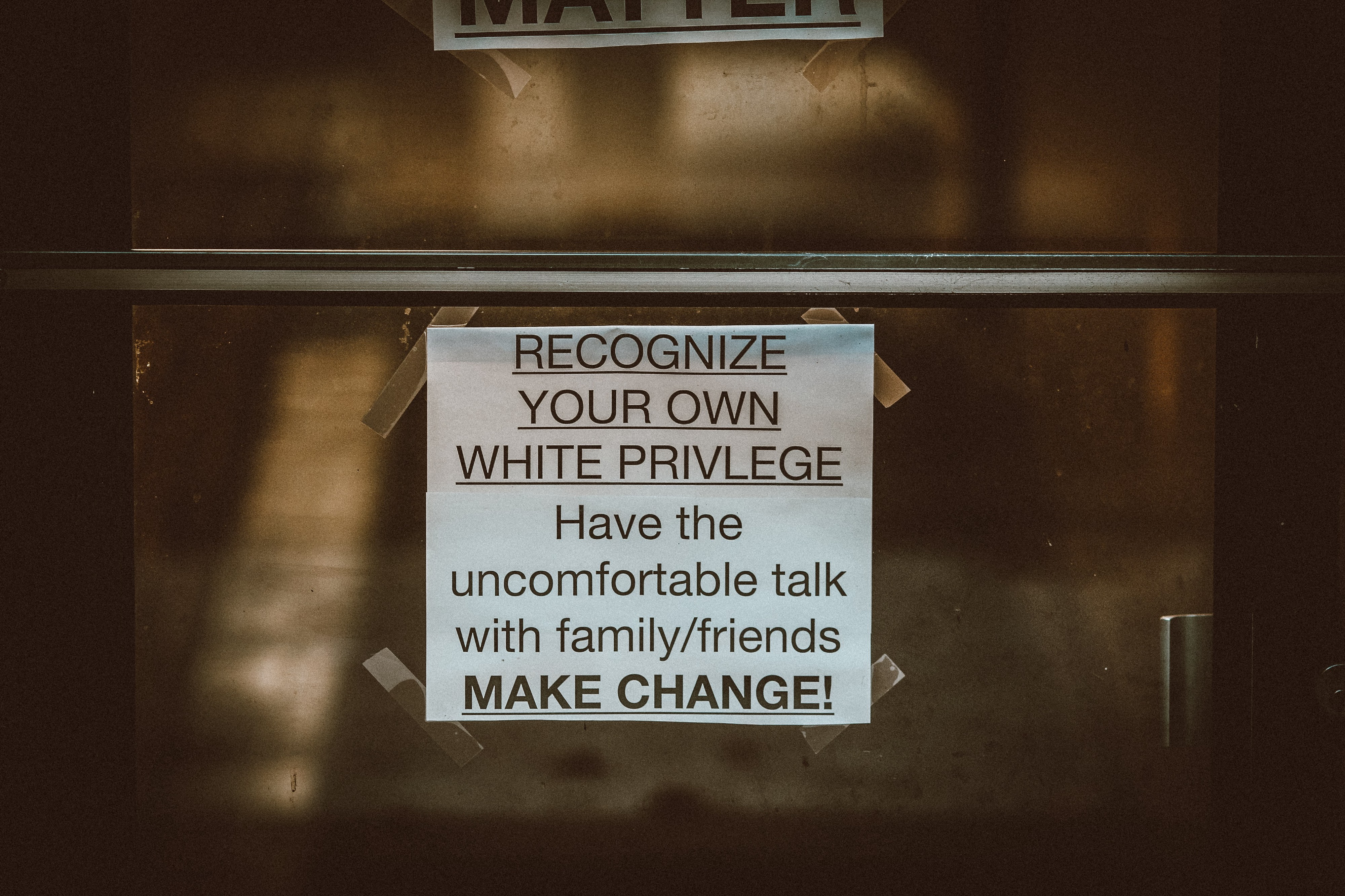 "A paper sign that says ""Recognize your own white privilege. Have the uncomfortable talk with family/friends. Make change!"""
