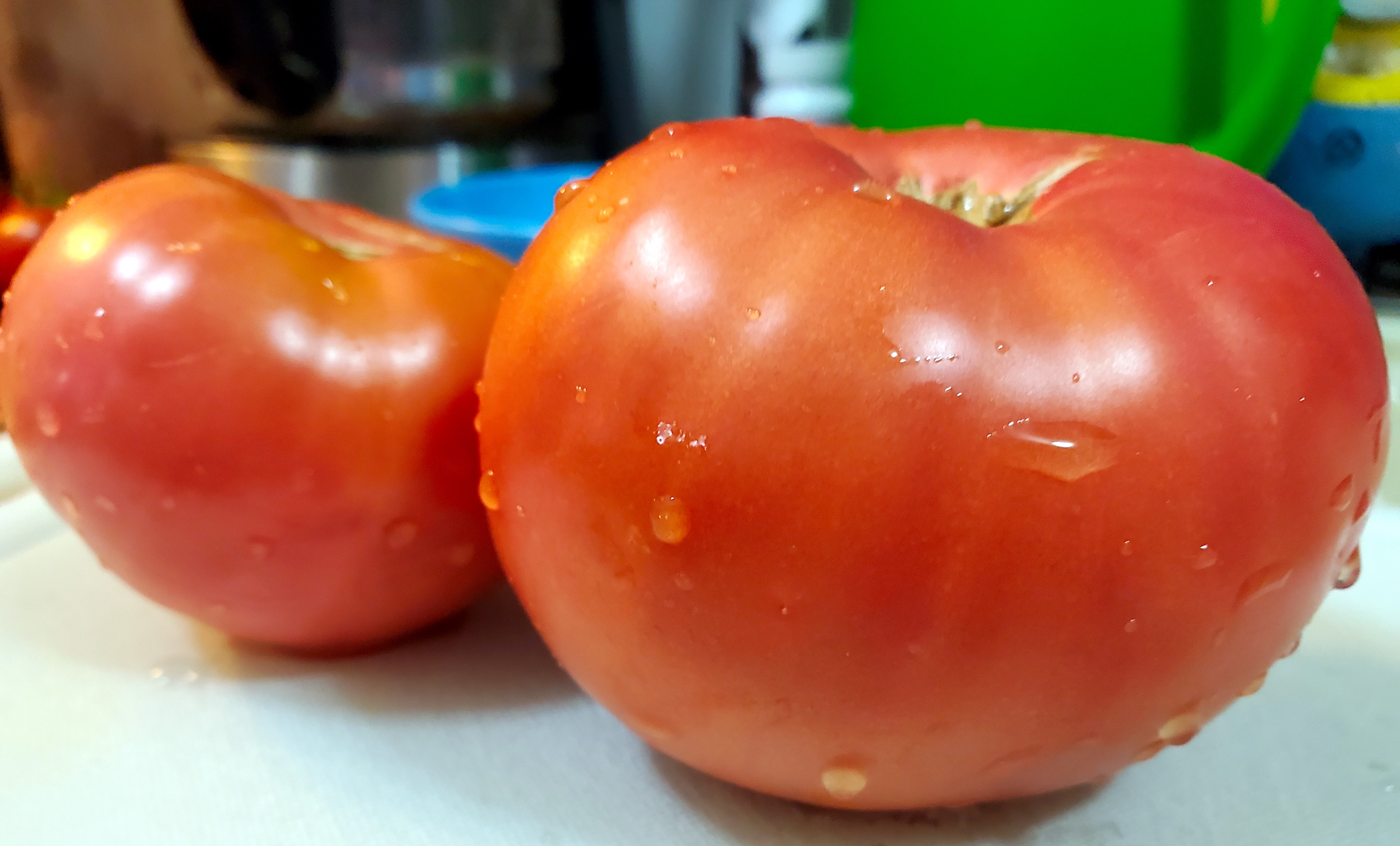 Two rinced Mortgage lifter tomatoes on a white cutting board