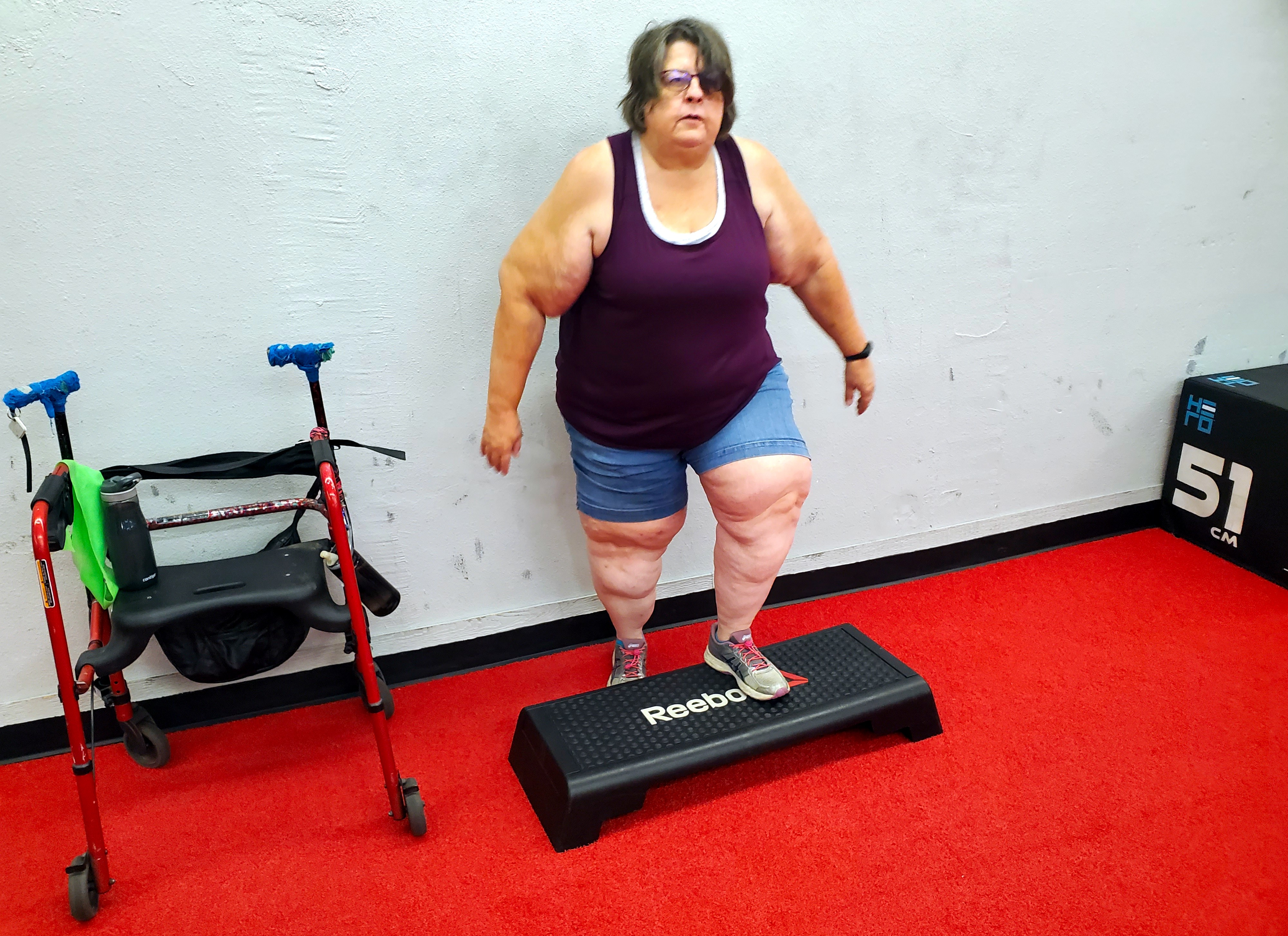 Older fat woman wearing a burgandy tank top and blue shorts stepping up on an exercise step next to a red wheeled walker