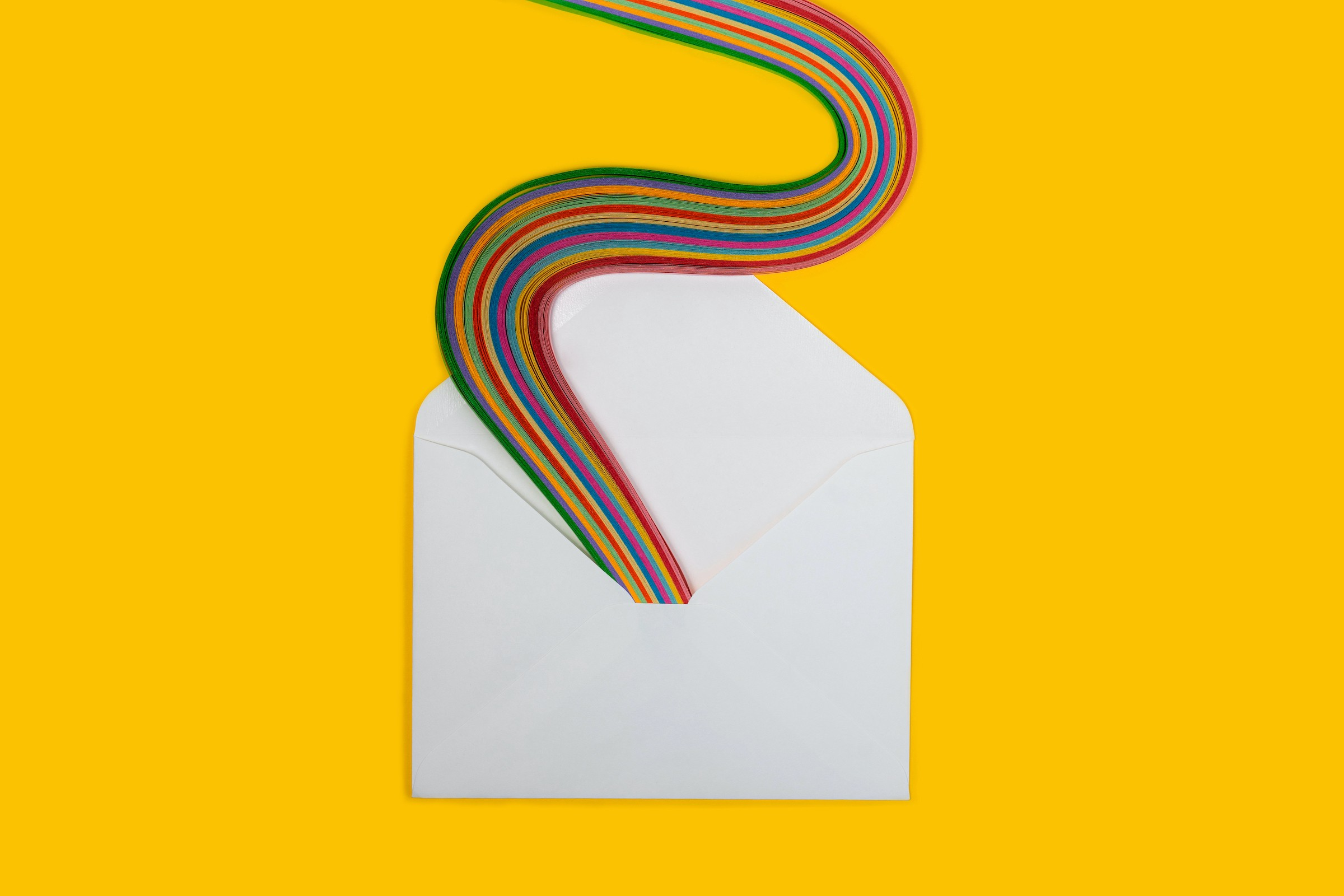 An open paper envelope on a yellow surface. A serpentine rainbow snakes its way out of the envelope.
