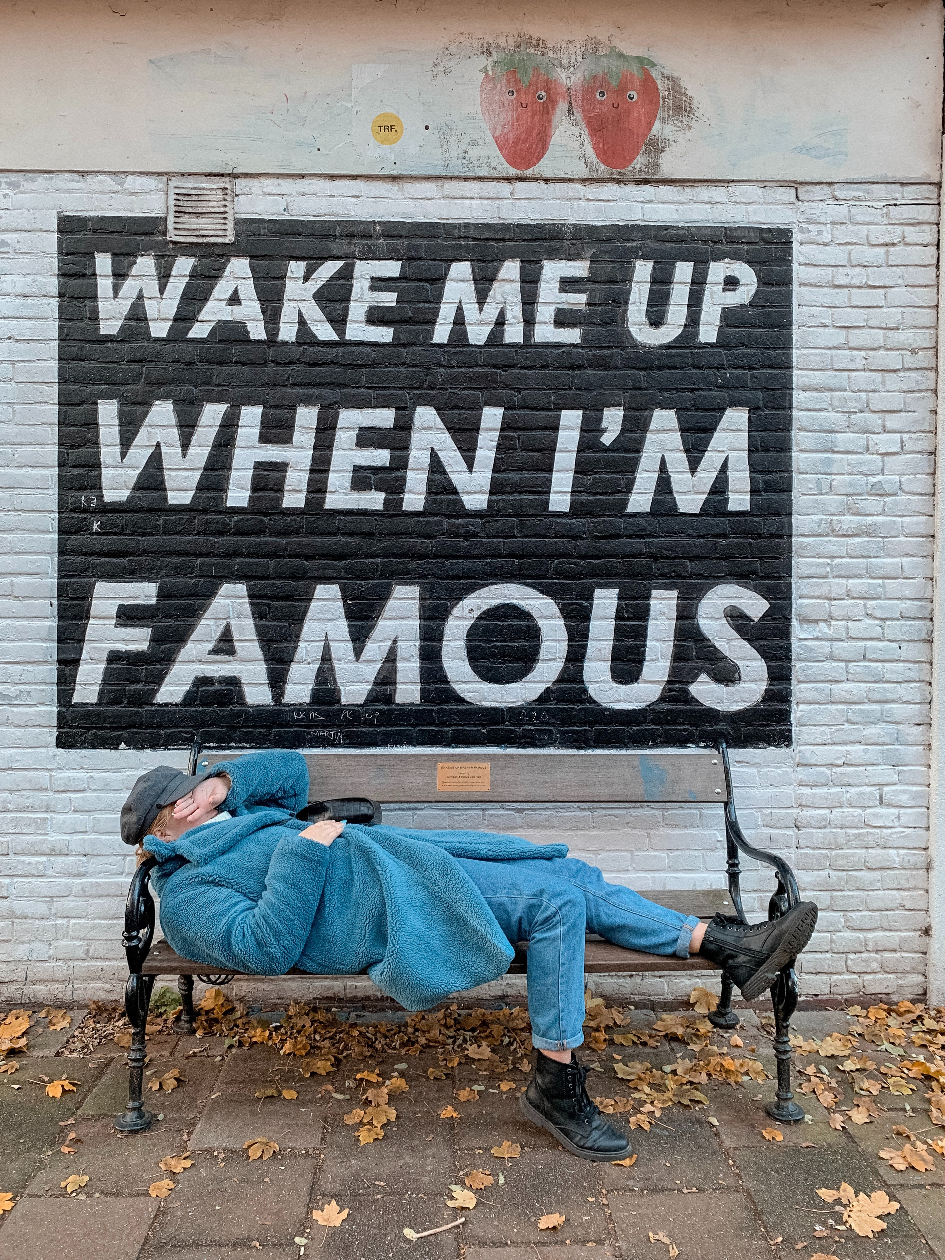 """A woman lying down on a park bench, with her hand over her face. There's an inscription on the wall saying """"Wake me up when I'm famous"""""""