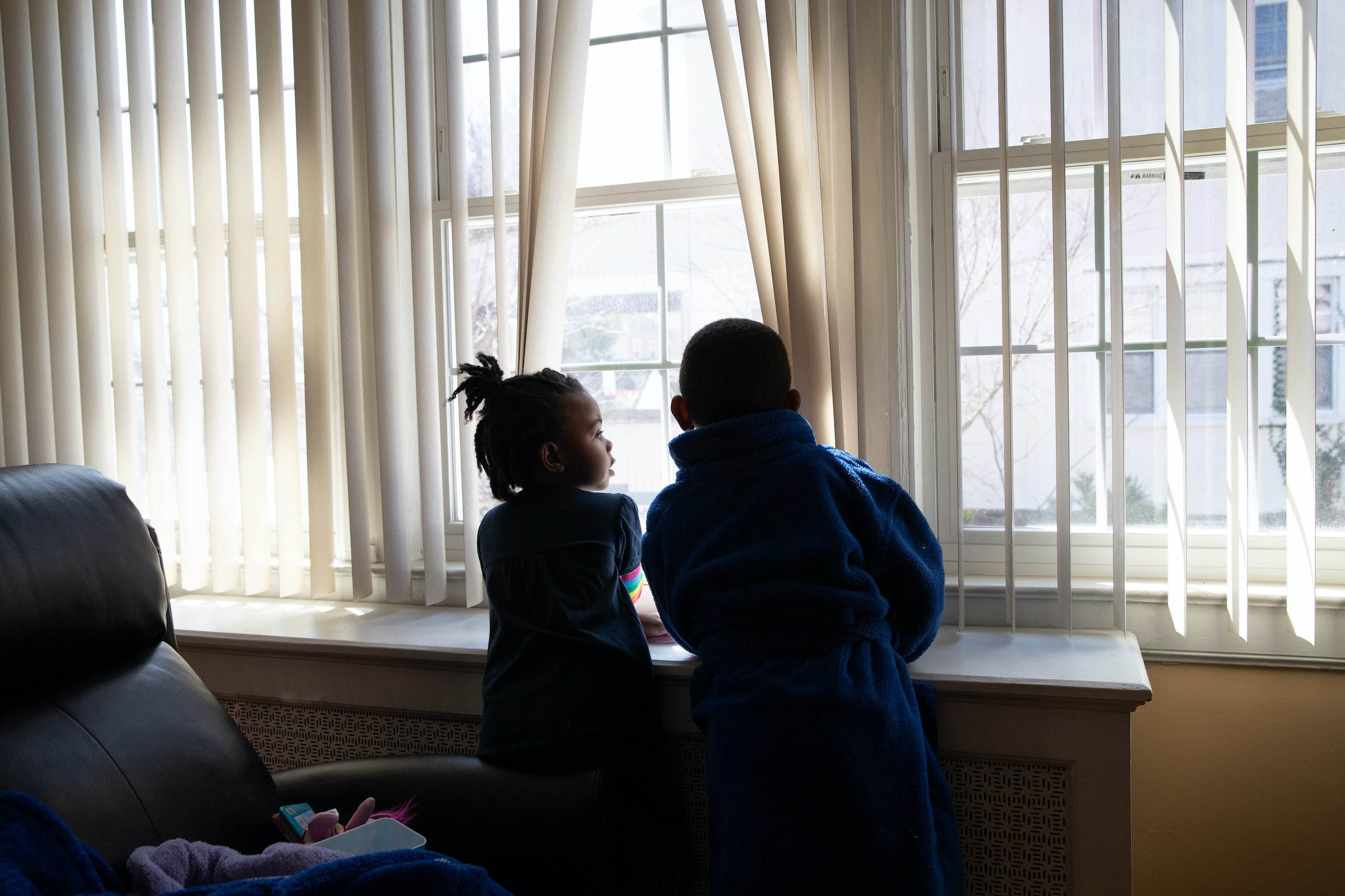 Two Black children holding vertical blinds apart to look out a window.