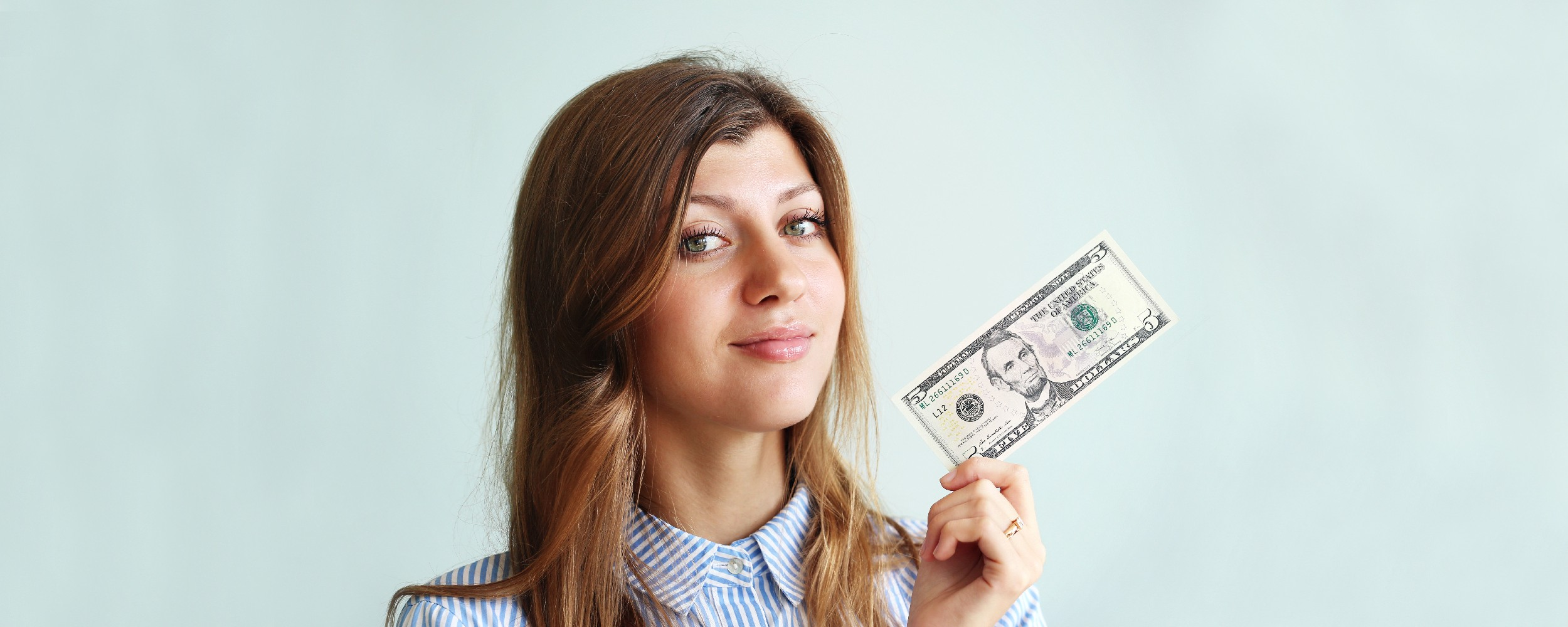 Woman holding five dollar bill