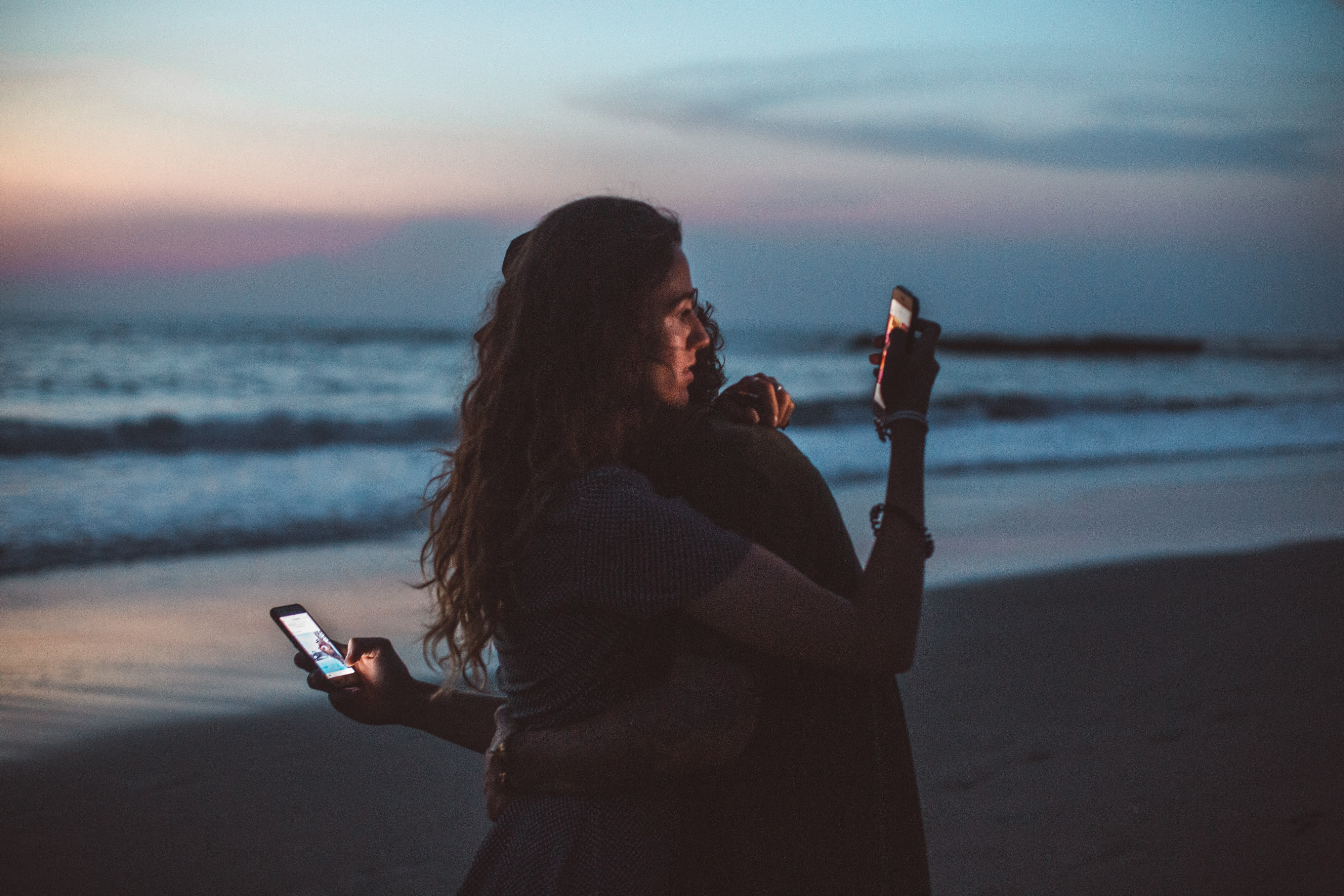 Young couple standing on a sandy beach, taking selfies against a sunset background.