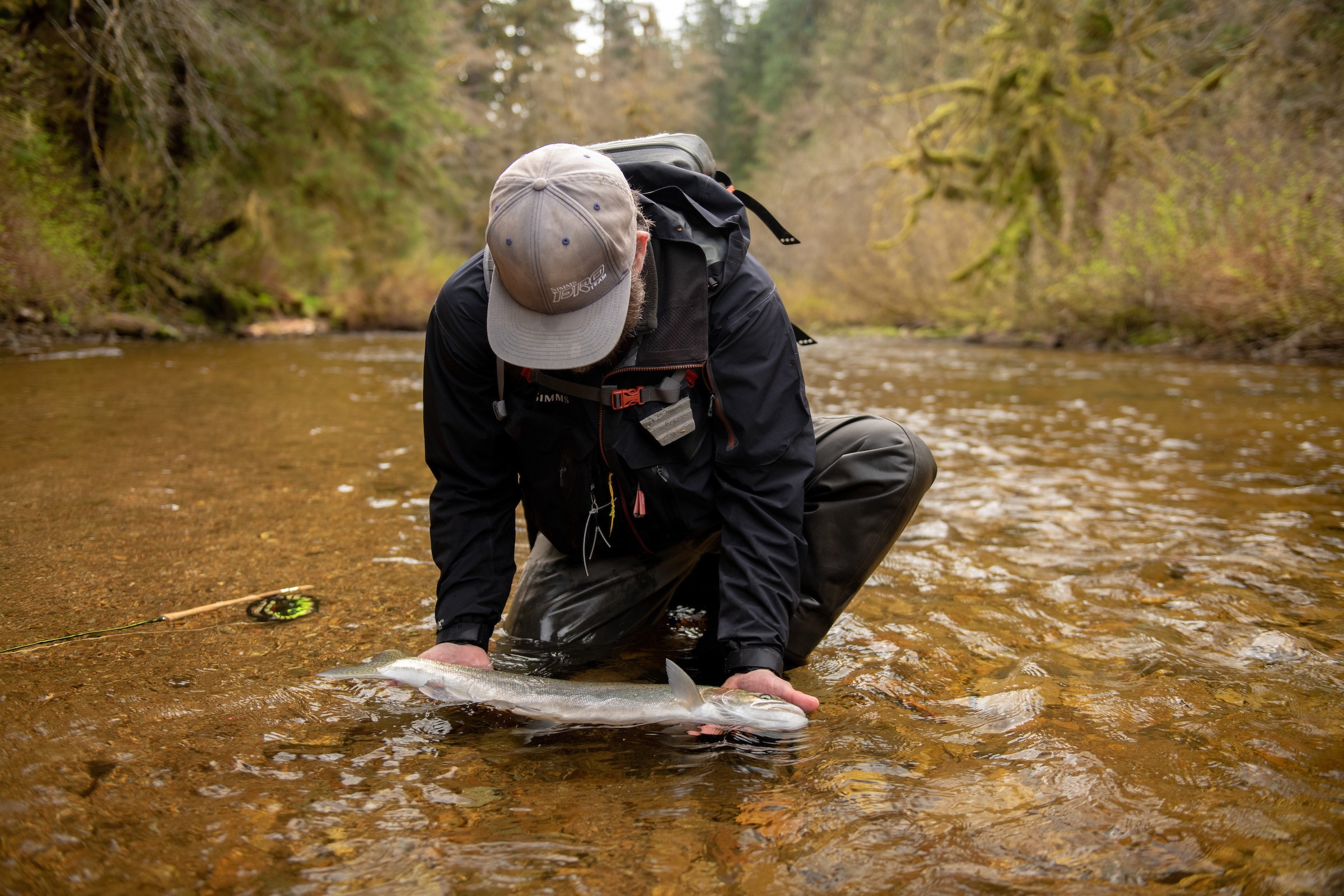 man holding a trout in the water