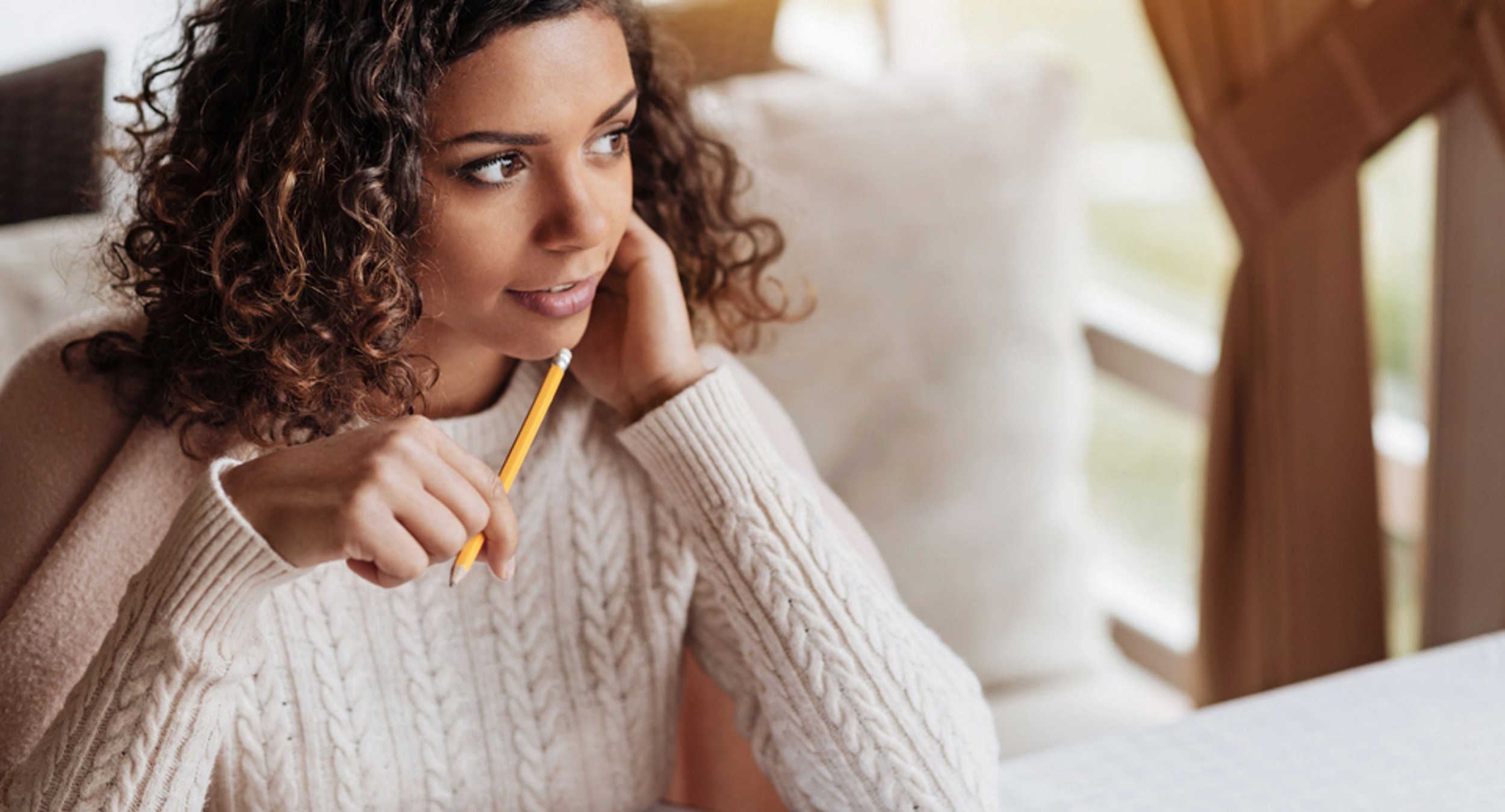 Photo of smiling female, holding pencil