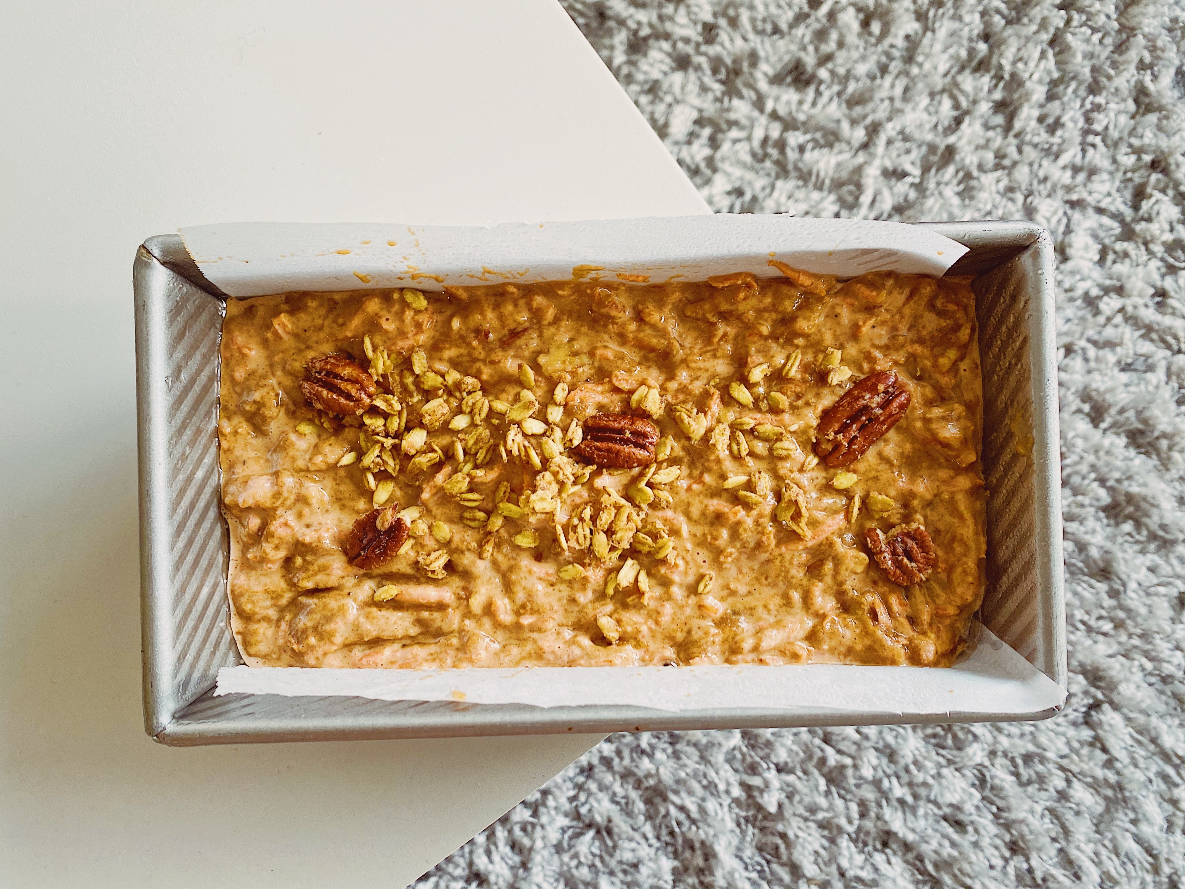 A carrot cake ready to be baked with a sprinkle of granola and 5 pecans.