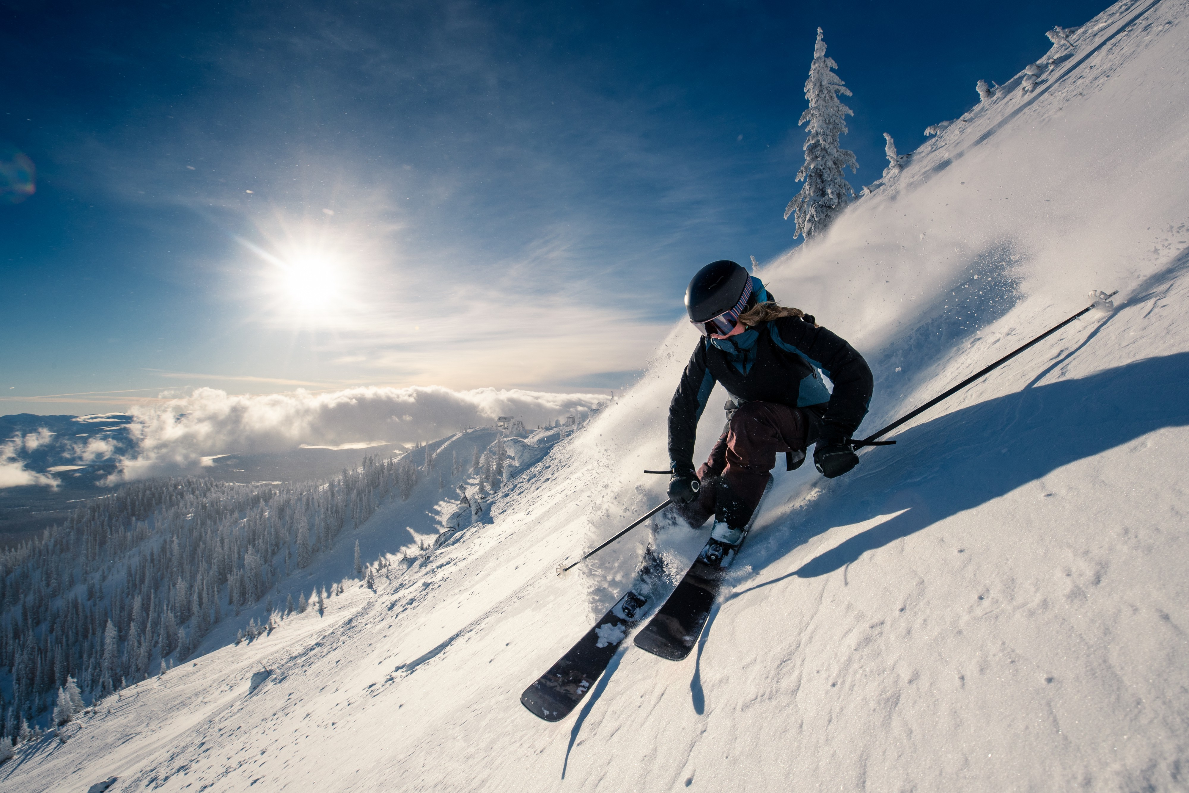 Skier cutting a turn on a slope with the sun in the background