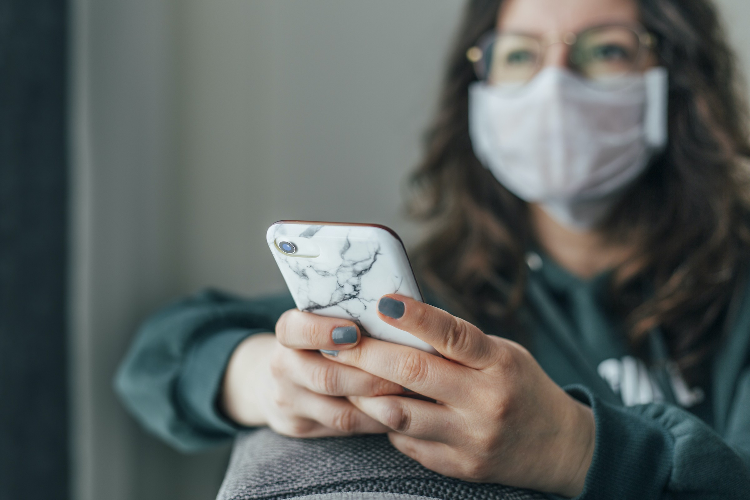 A person wearing a face mask, using their phone. They seem to have an optimistic expression.