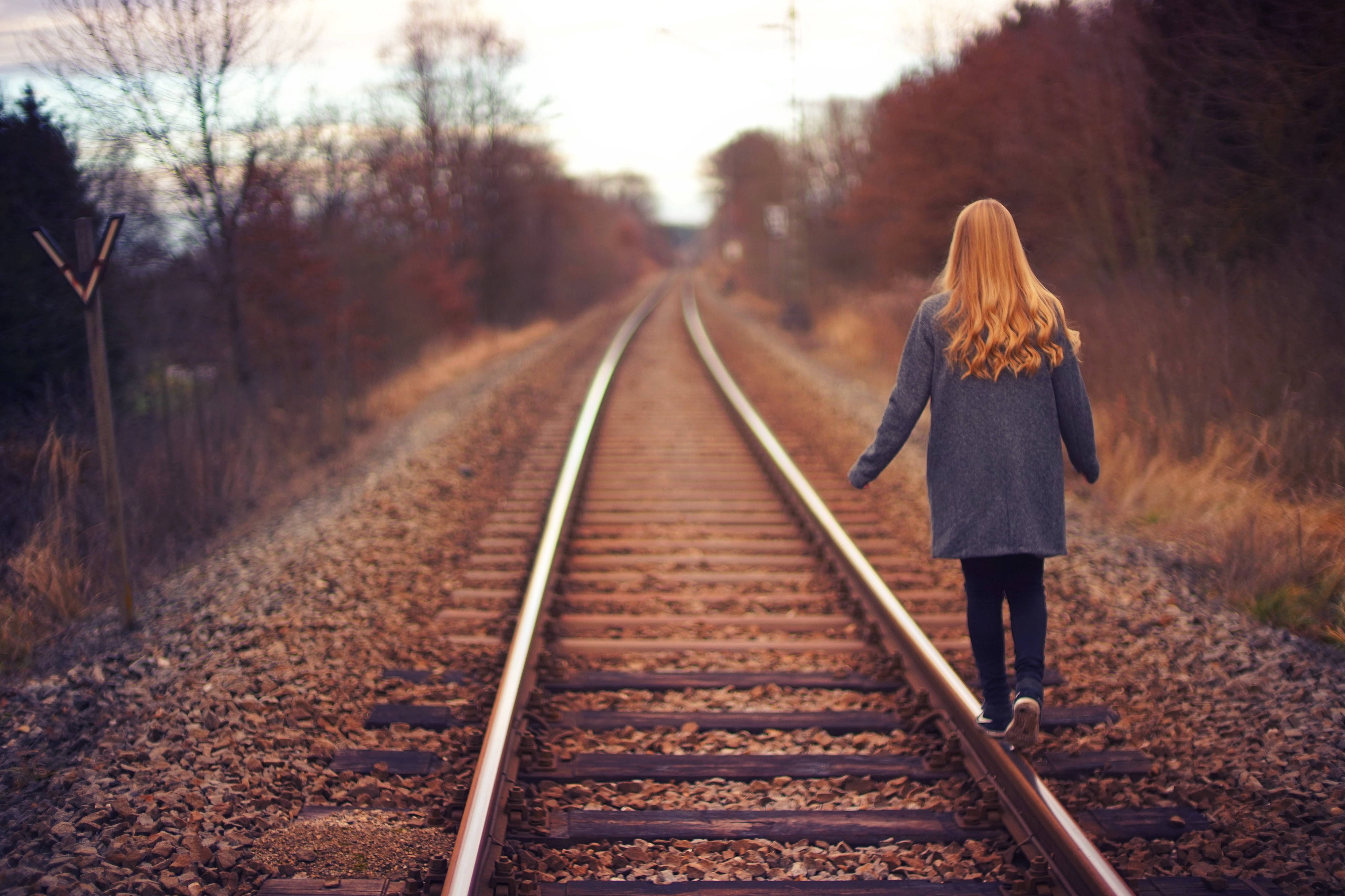 A woman with long red and a grey coat, balances on railroad tracks. Photo by Johannes Plenio on Unsplash