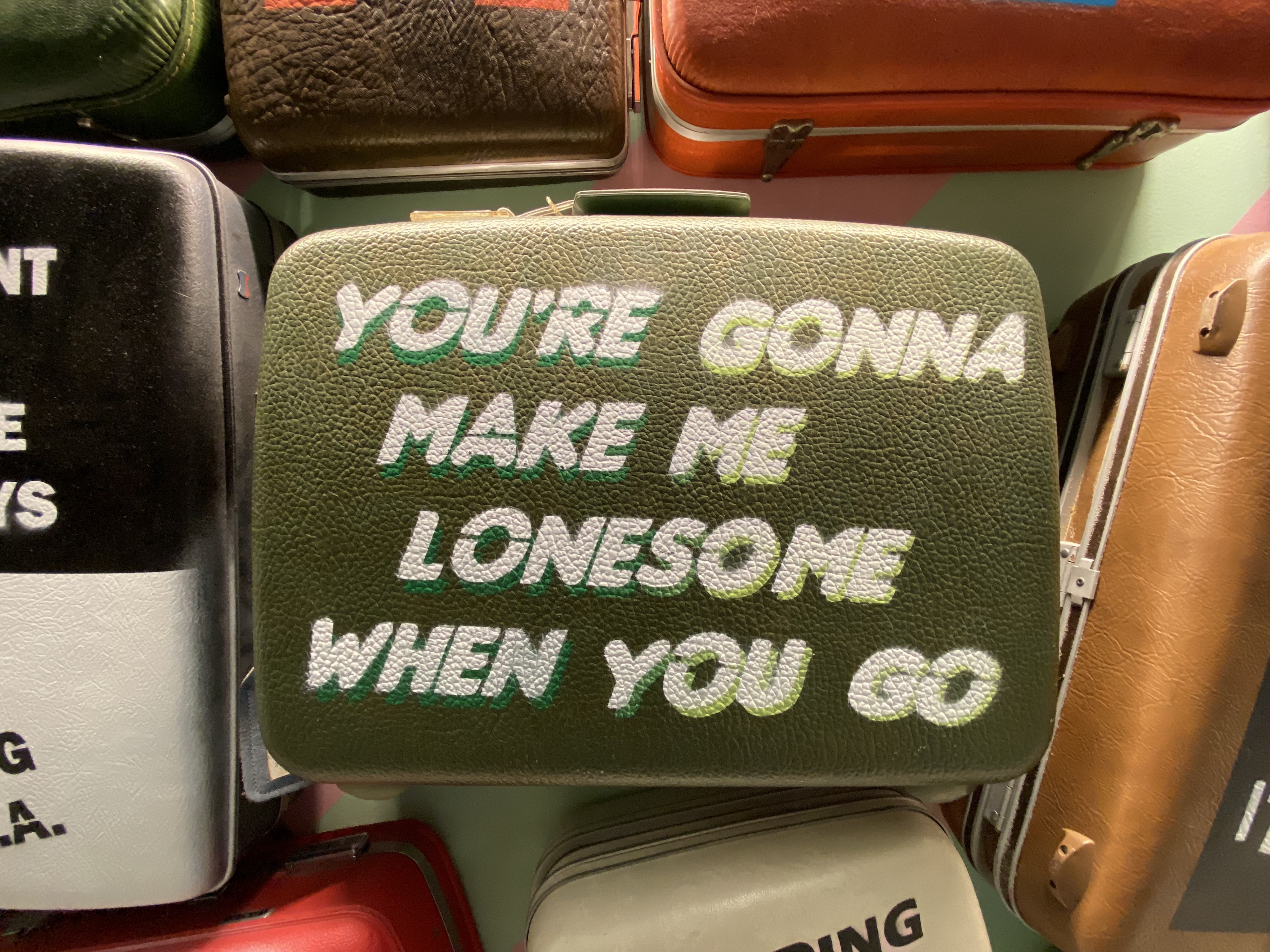 """A vintage suitcase (tucked in a pile) reads, """"You're gonna make me lonesome when you go."""""""