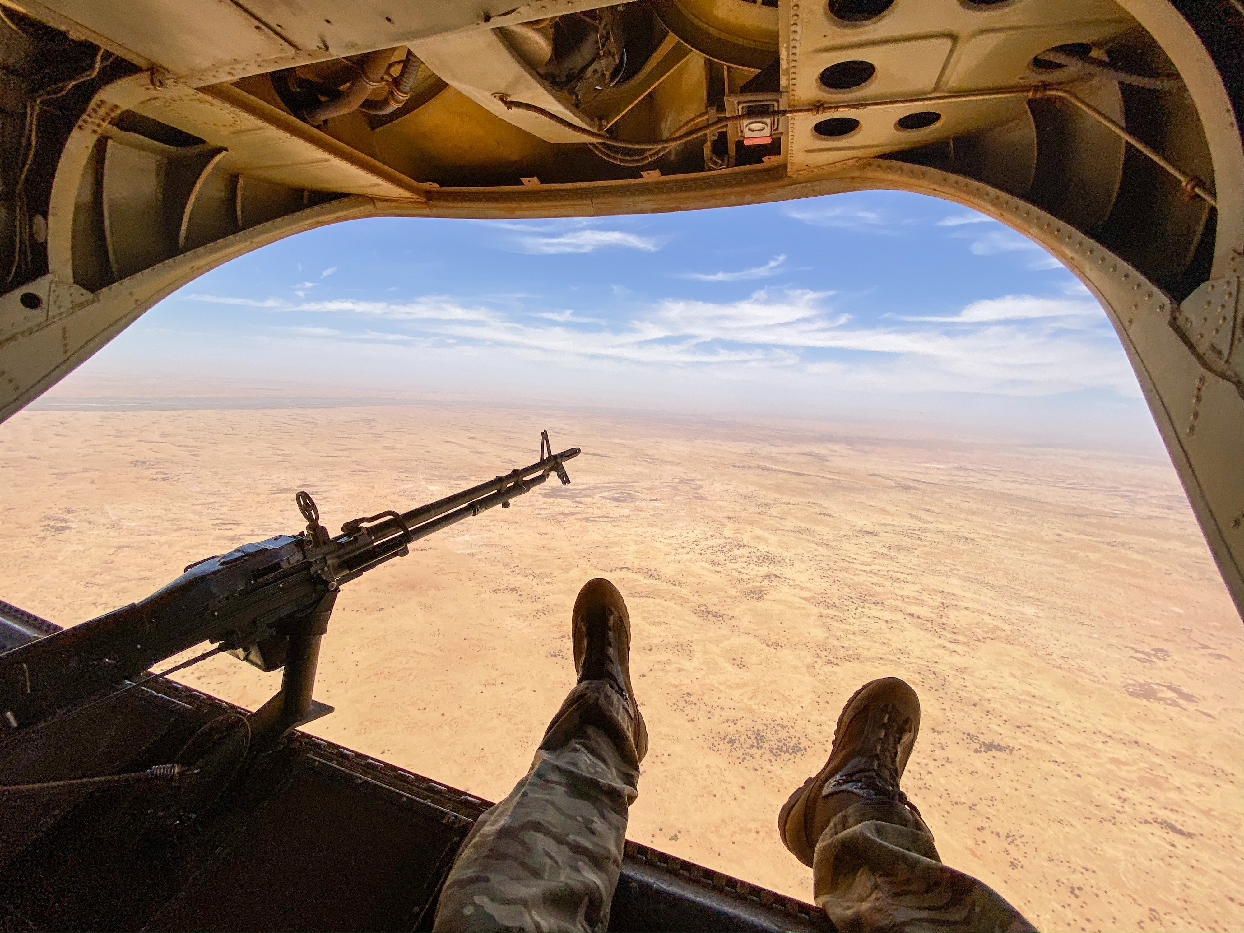 An image of a Chinook helicopter flying over the desert.
