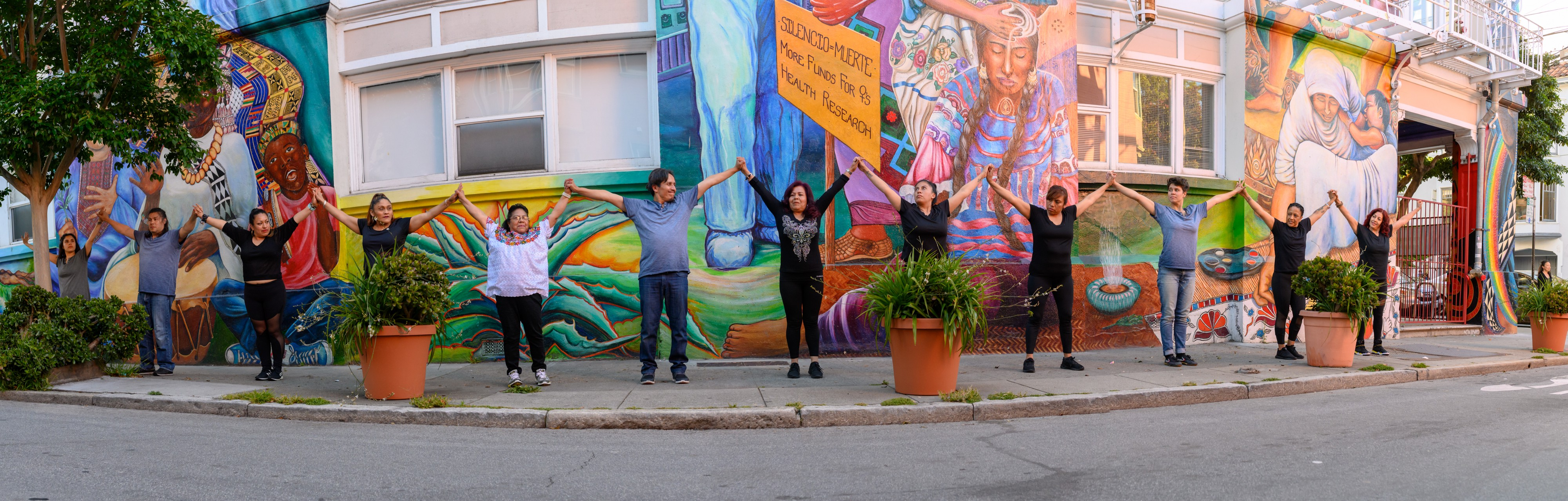 Group of performers on a sidewalk in front of a street mural holding up linked hands