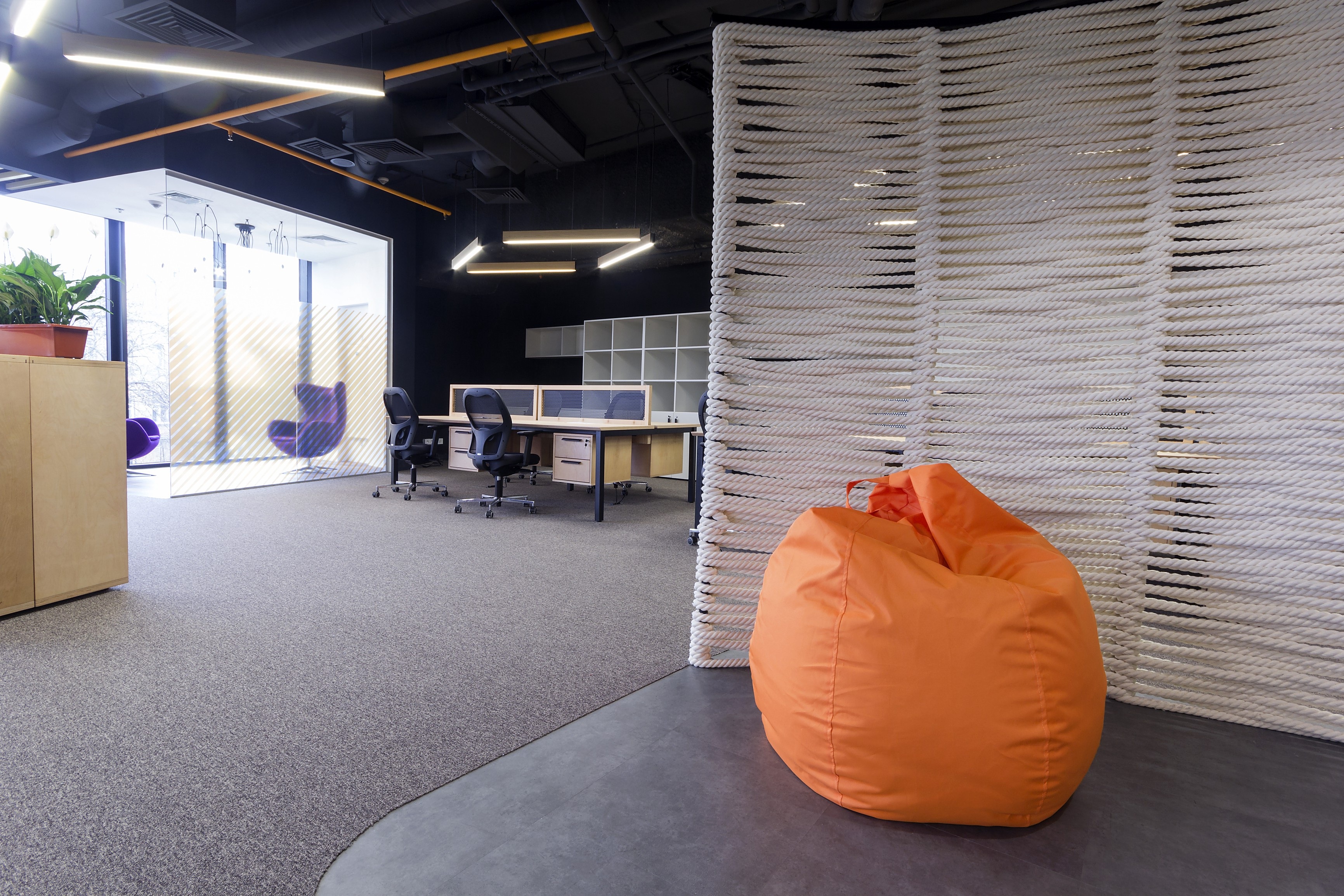 An orange beanbag foreground in an empty office. How the workspace should evolve in the now normal is a question of values