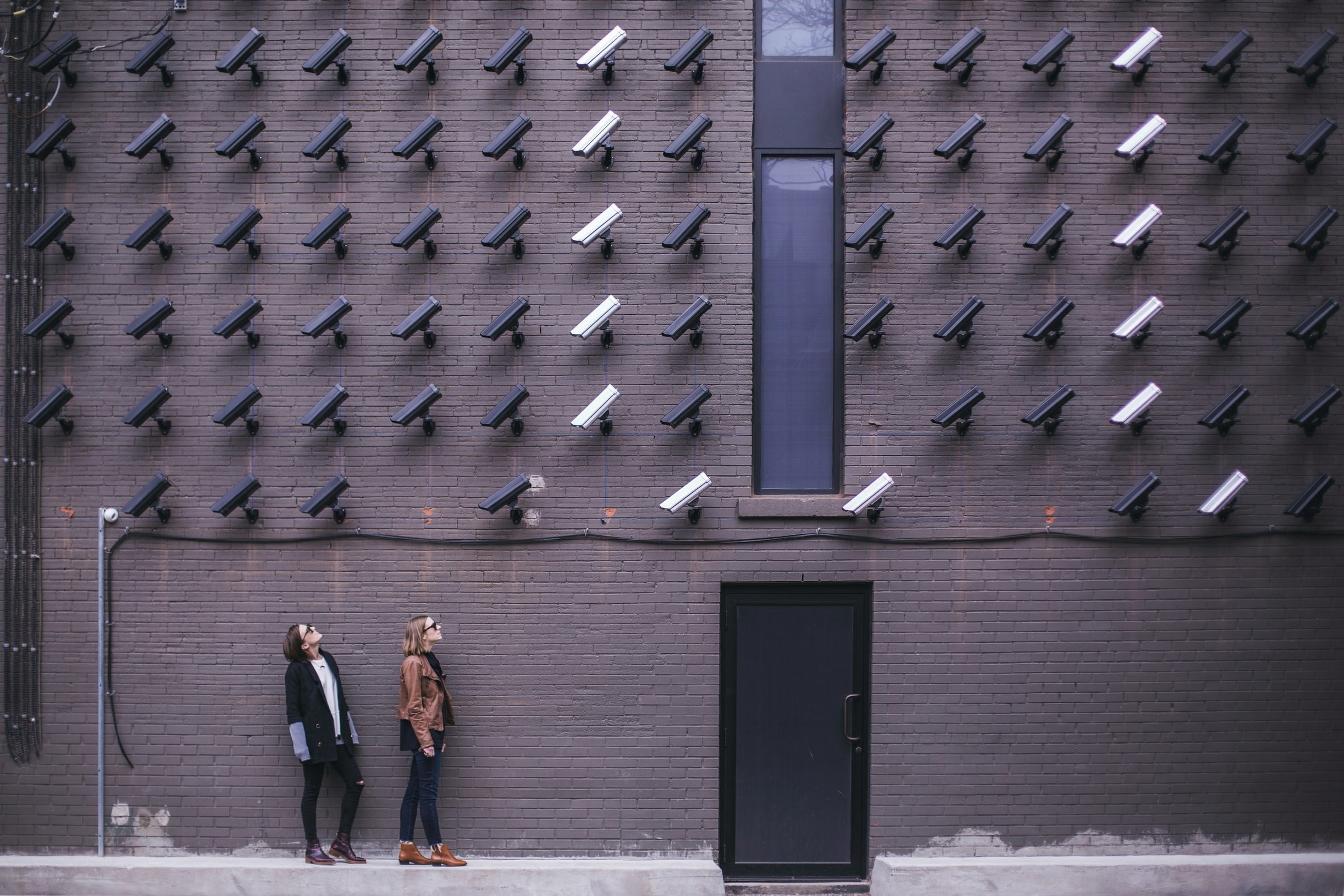 Two women looking at security cameras